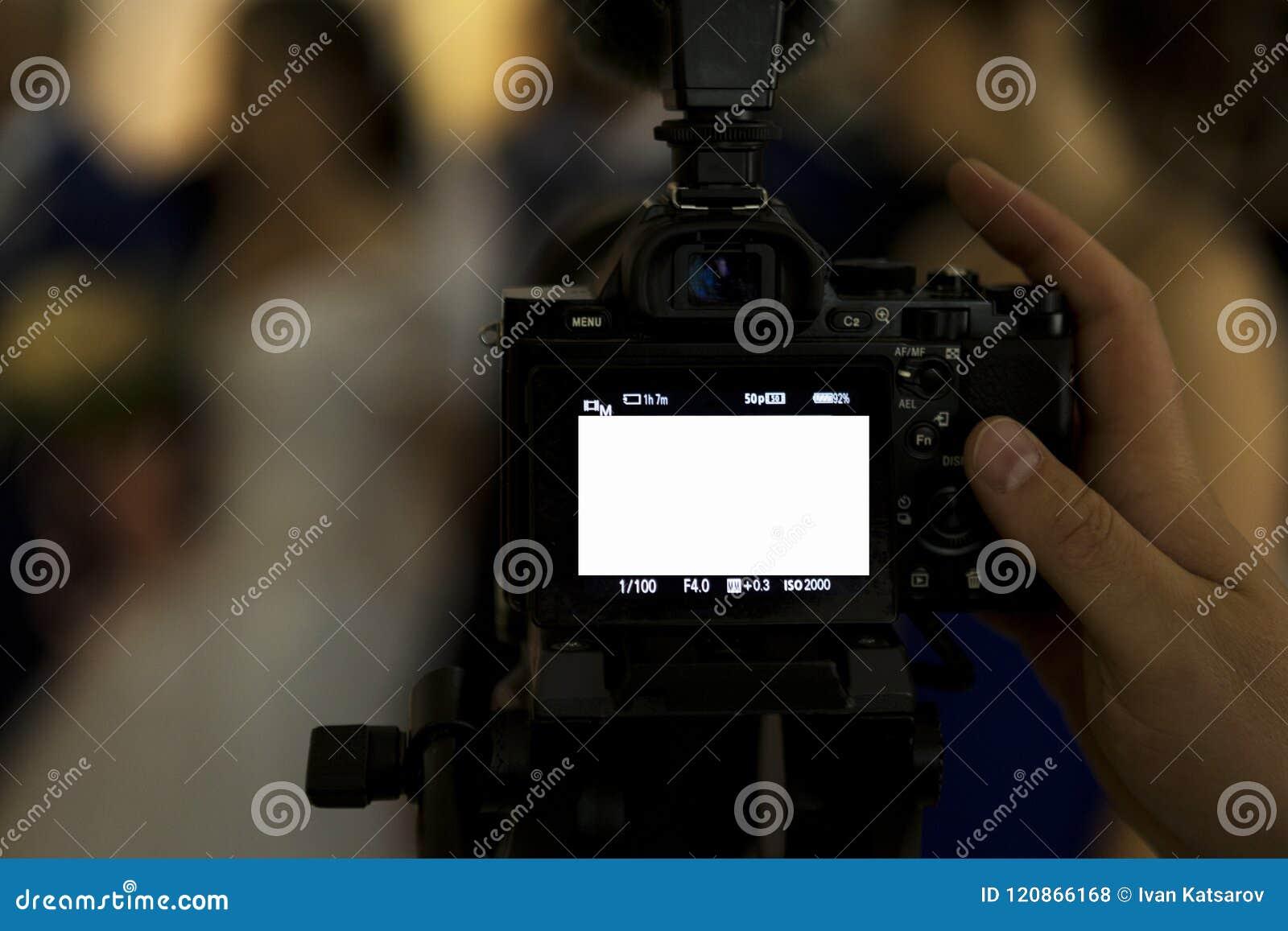 Un photographe, un photographe ou un journaliste reflète un événement d intérieur d appareil-photo