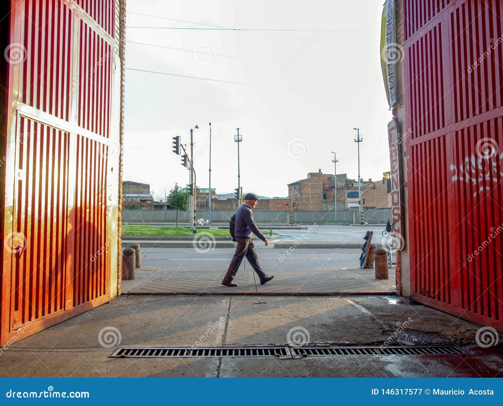 Un piéton croise devant la grande porte orange