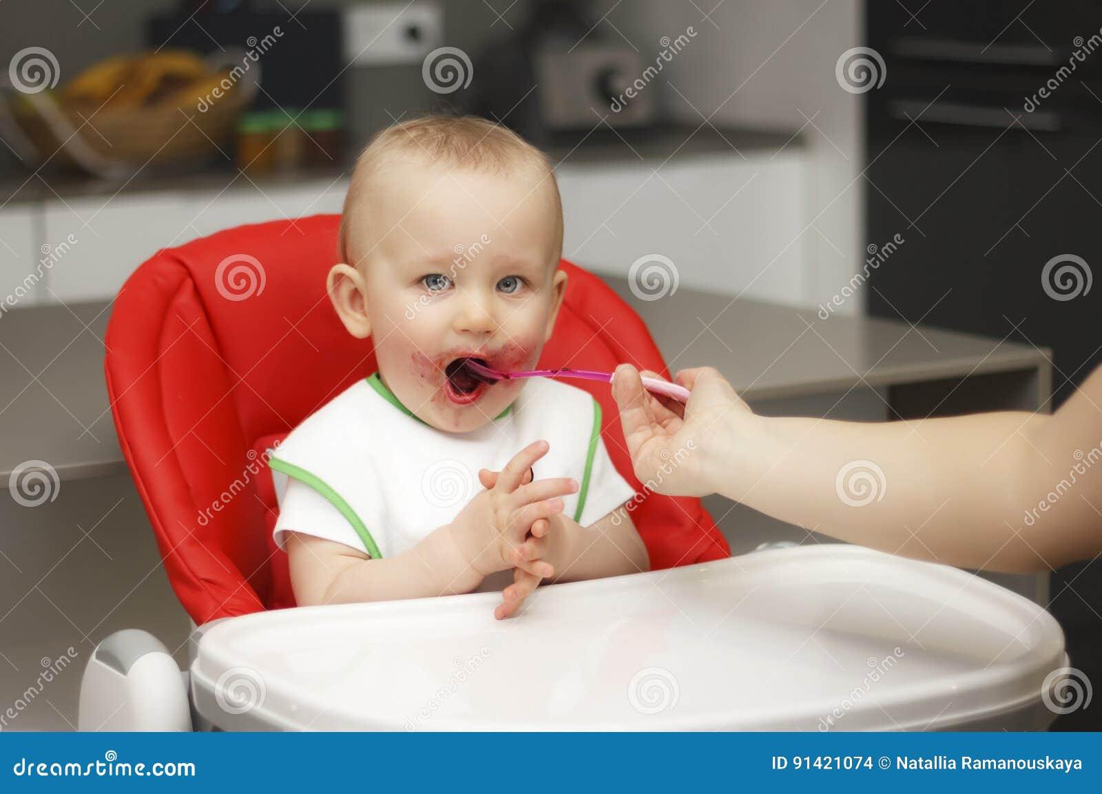 Un piccolo bambino mangia l inceppamento ed il cereale, si siede su un seggiolone