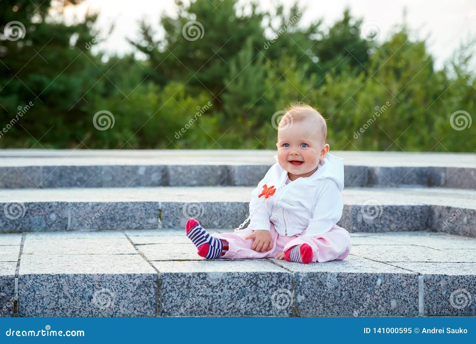 Un piccolo bambino si siede sulla terra