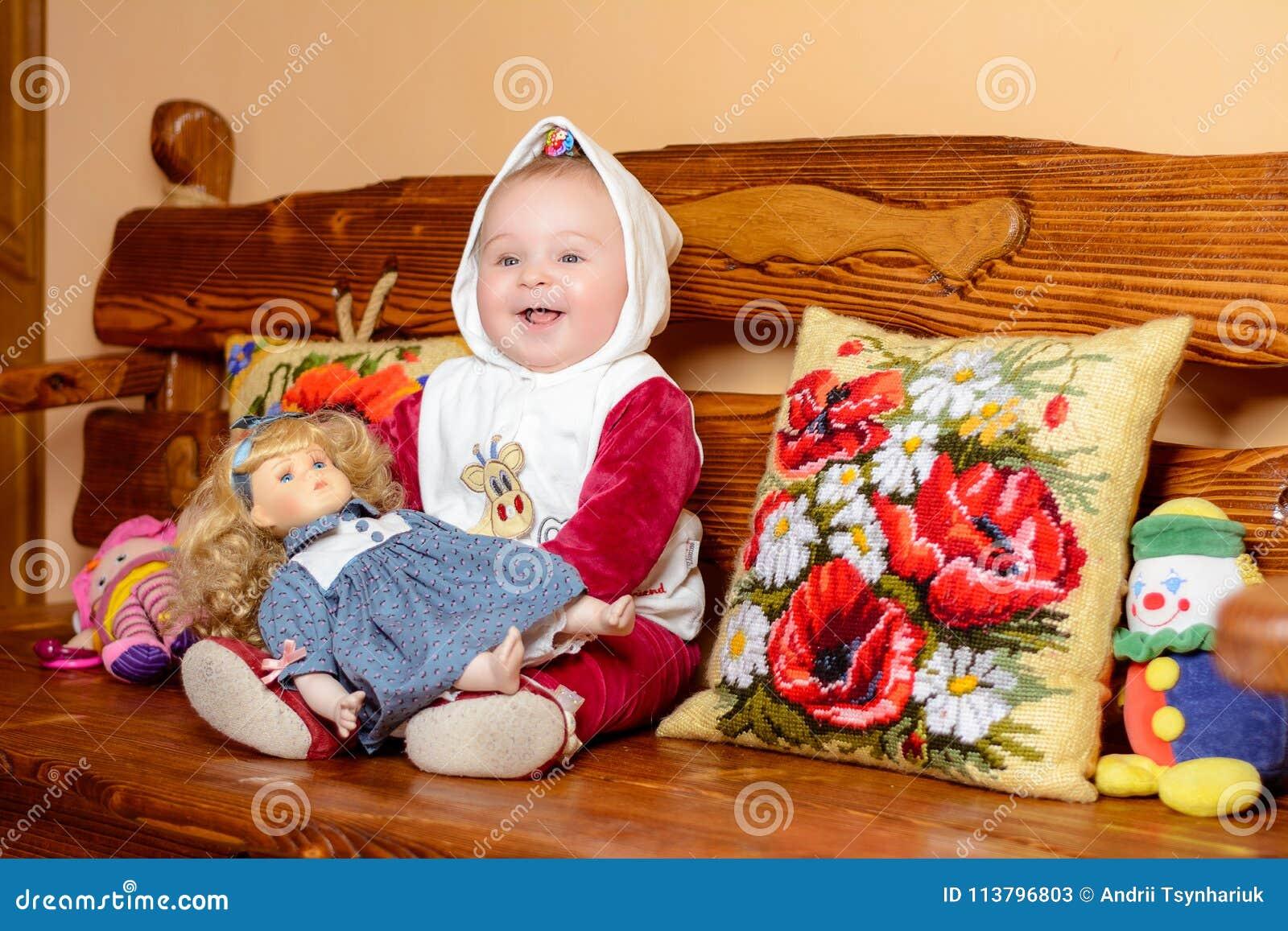 Un piccolo bambino in uno scialle che si siede su un sofà con i cuscini ricamati