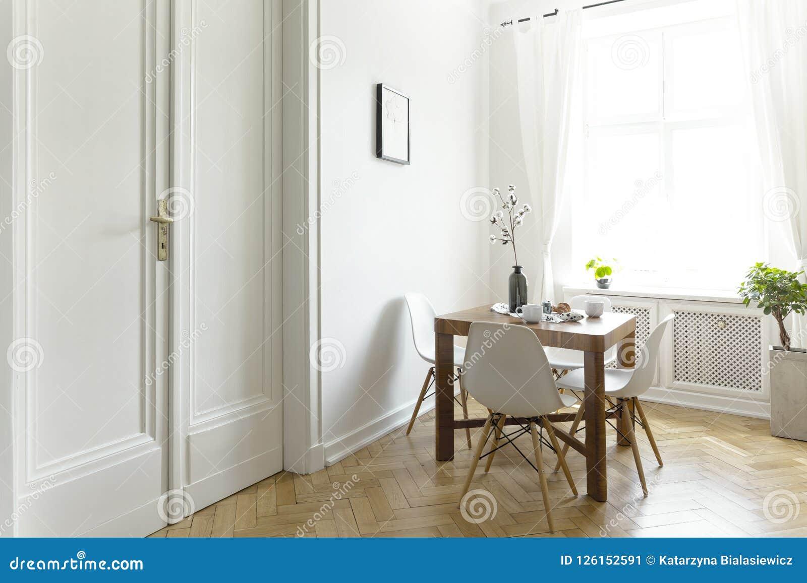 Tavolo Legno Sedie Bianche.Un Piccolo Tavolo Da Pranzo Di Legno Con Le Sedie In Un Interno