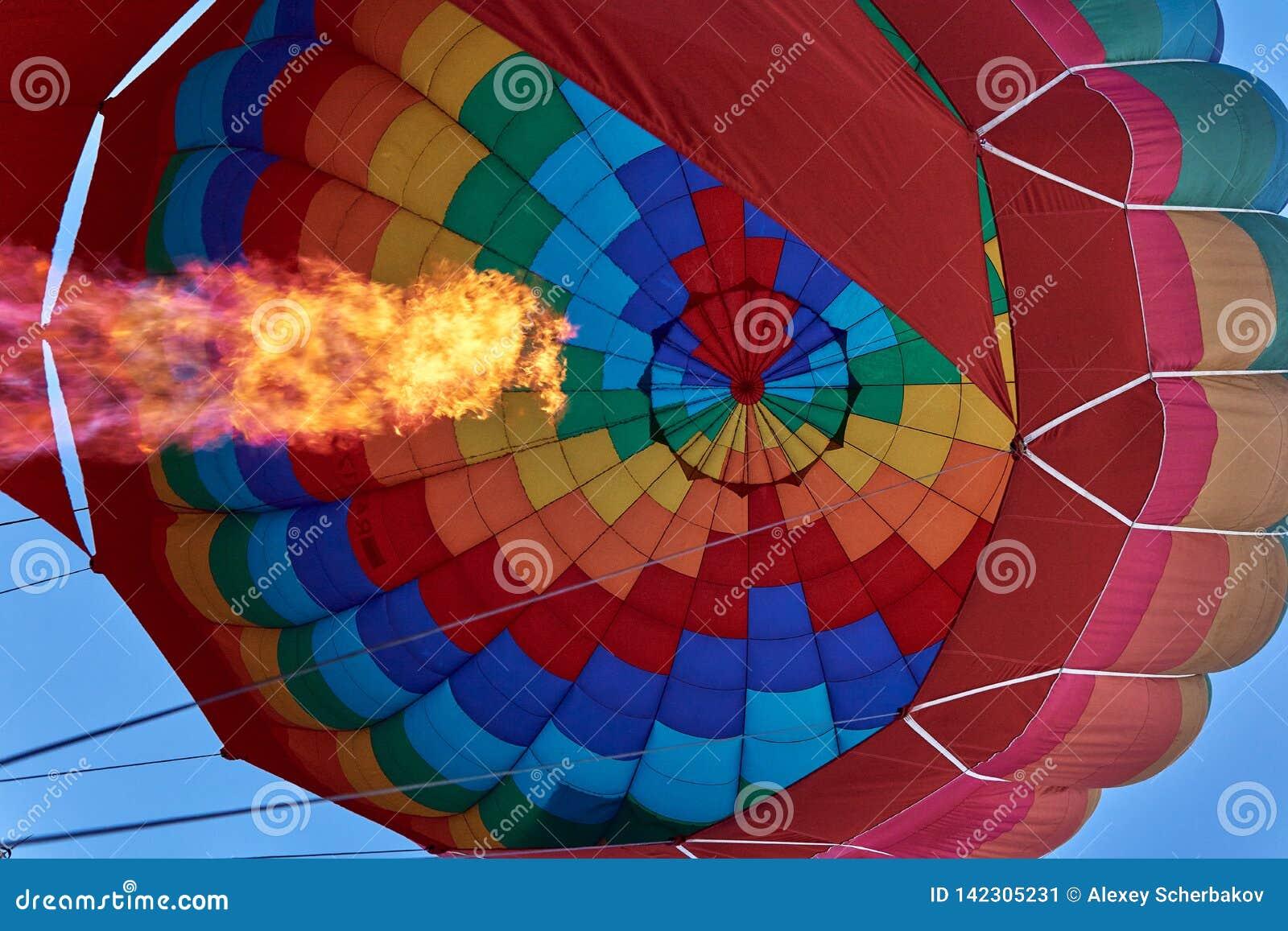 Un pilar de la llama de un mechero de gas infla un globo multicolor enorme