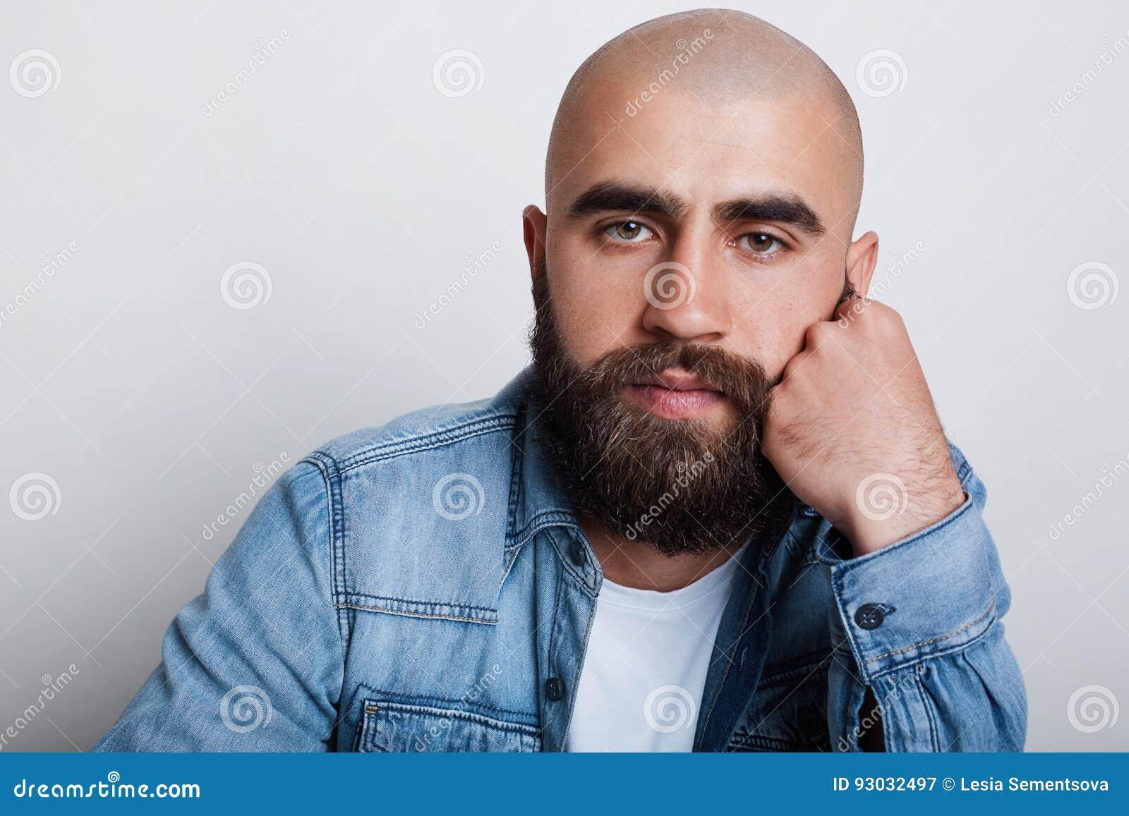 Un plan rapproché horizontal de l homme chauve bel ayant les yeux foncés de charme, les sourcils noirs épais et la chemise de por