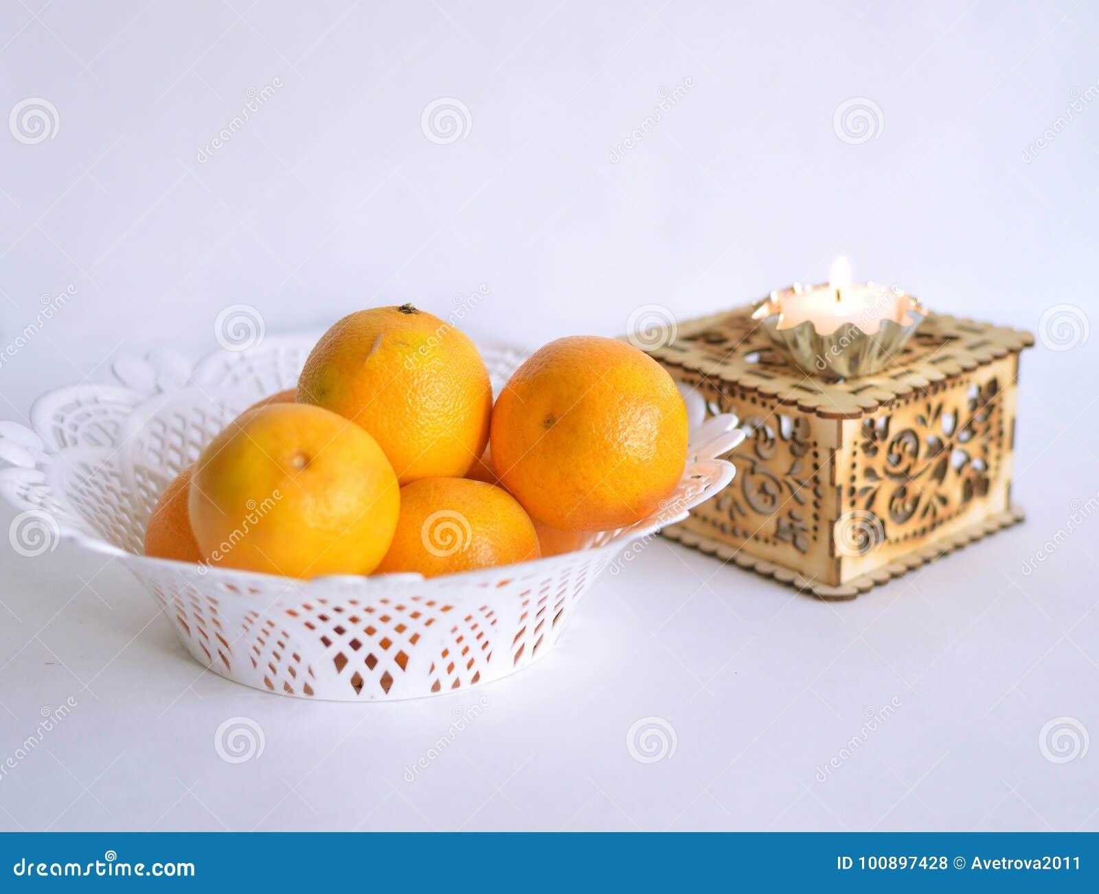 Un Plat Blanc Des Oranges A Cote D Une Boite Avec Une Petite Bougie