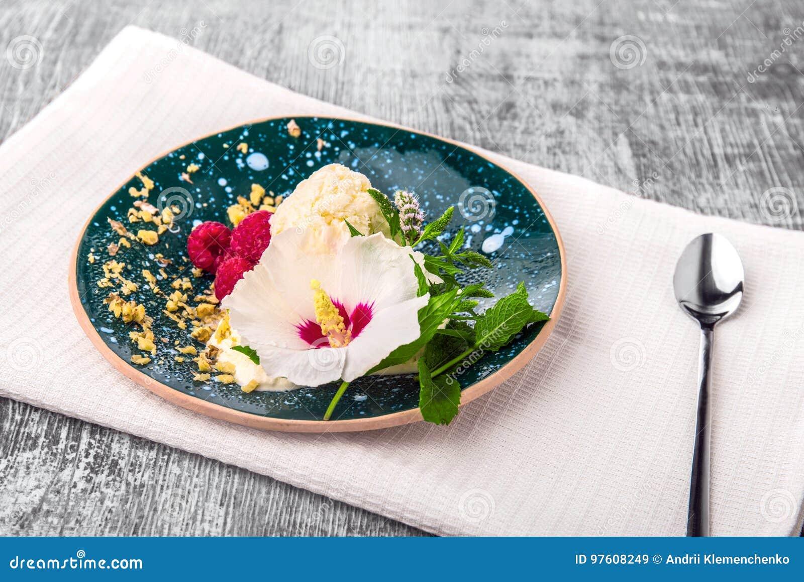 Un plat complètement d une crème glacée avec les framboises roses douces sur un tissu blanc et sur un fond en bois Casse-croûte o