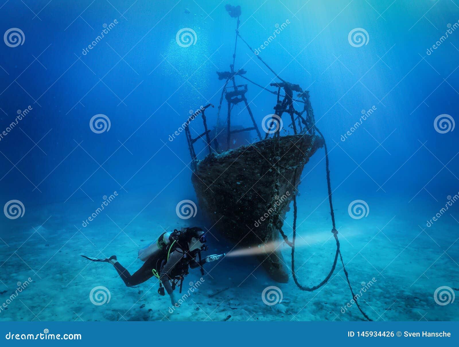 Un plongeur autonome féminin explore un naufrage submergé