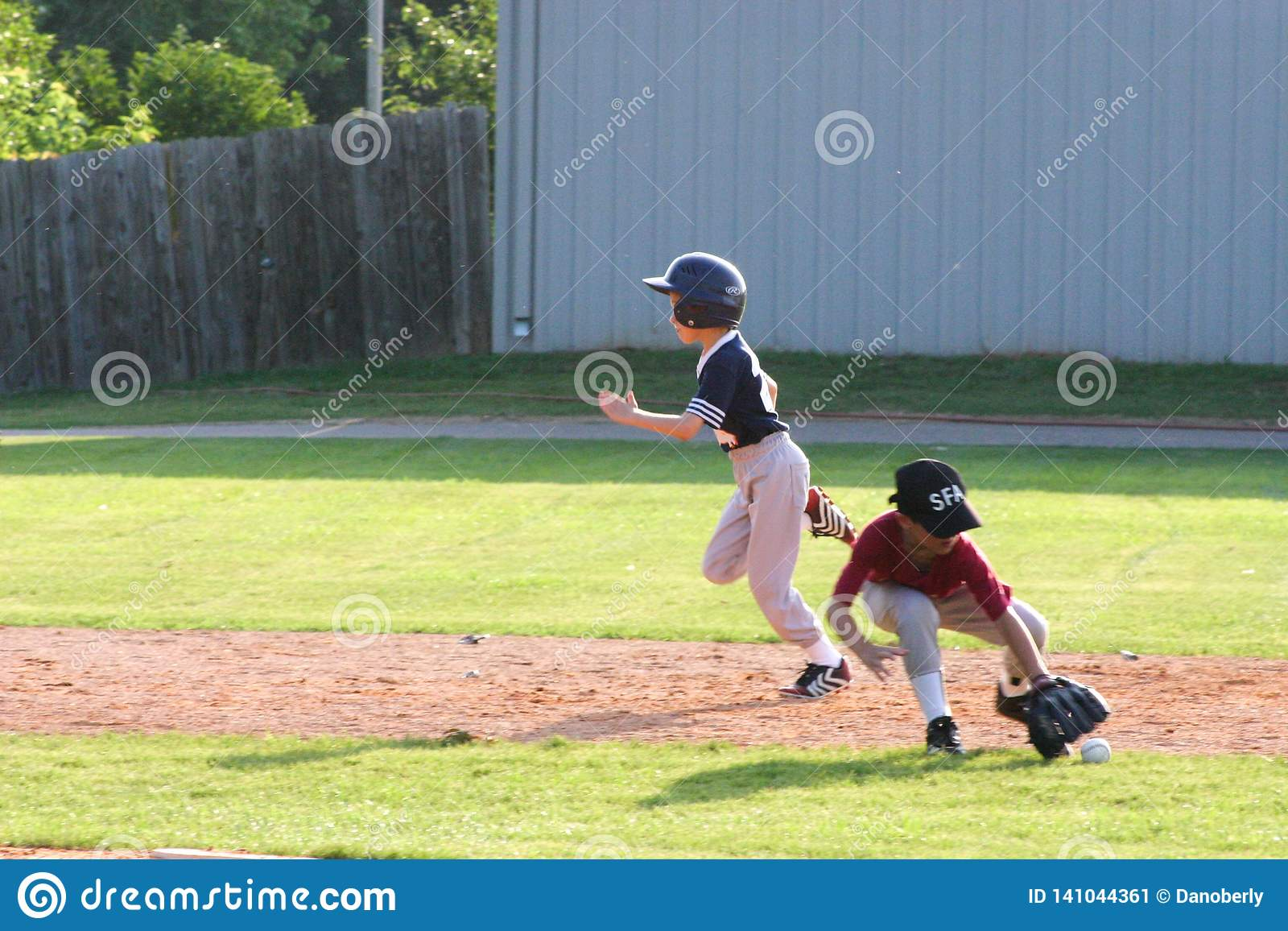 Un poco del giocatore di softball della piccola lega per la terza base mentre la seconda base raggiunge per la palla