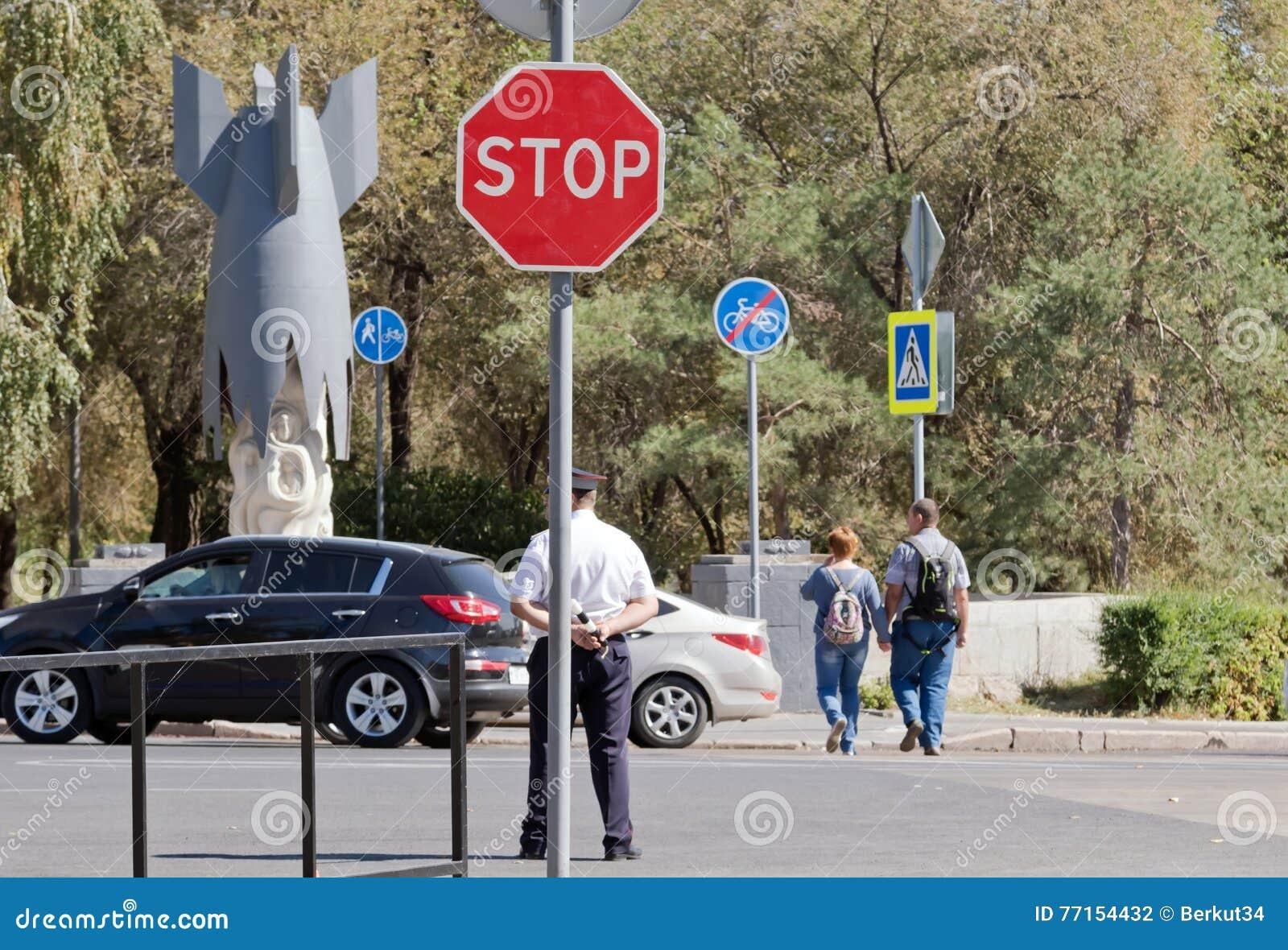 Un policier se trouve au tournant avec une tige dans des mains sur