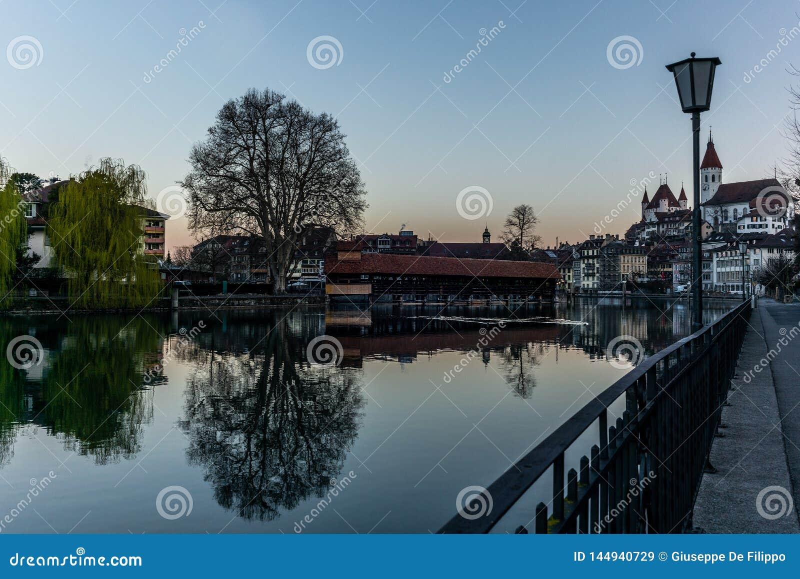 Un pont en bois traversant la rivière Aare avec le château de Thun à l arrière-plan tôt le matin