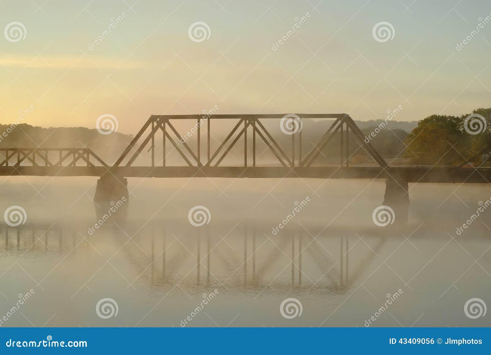 Un ponte della ferrovia sopra un fiume nebbioso e nebbioso Mo in anticipo