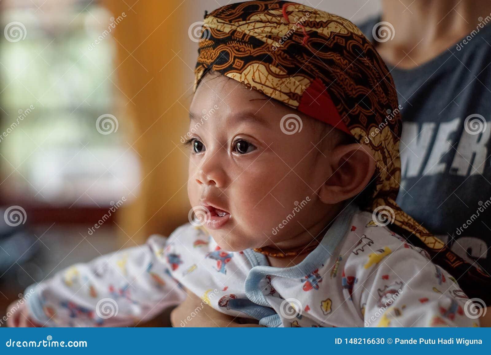 Un portrait d un mois-vieux b?b? 3 montrant un Blangkon de sourire et de port Blangkon est une b?che principale typique d ?le de