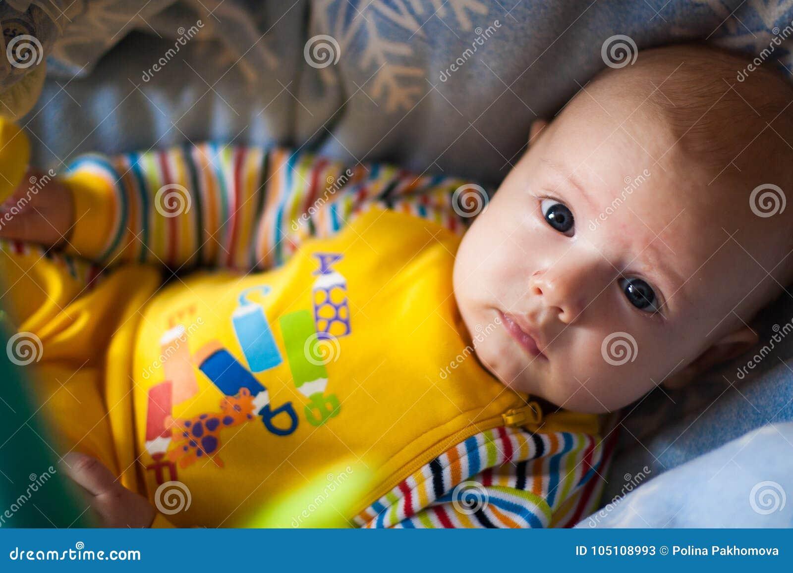 Un portrait d un petit garçon se situant dans une huche nous regardant