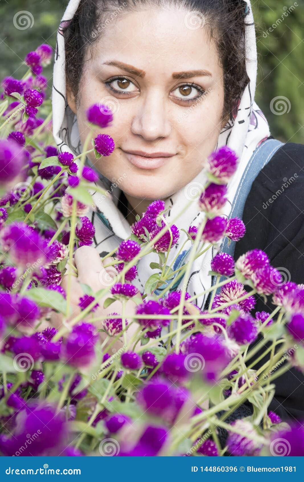 Un portrait d une jeune belle femme musulmane dans un châle blanc devant le tir vertical de fleurs pourpres