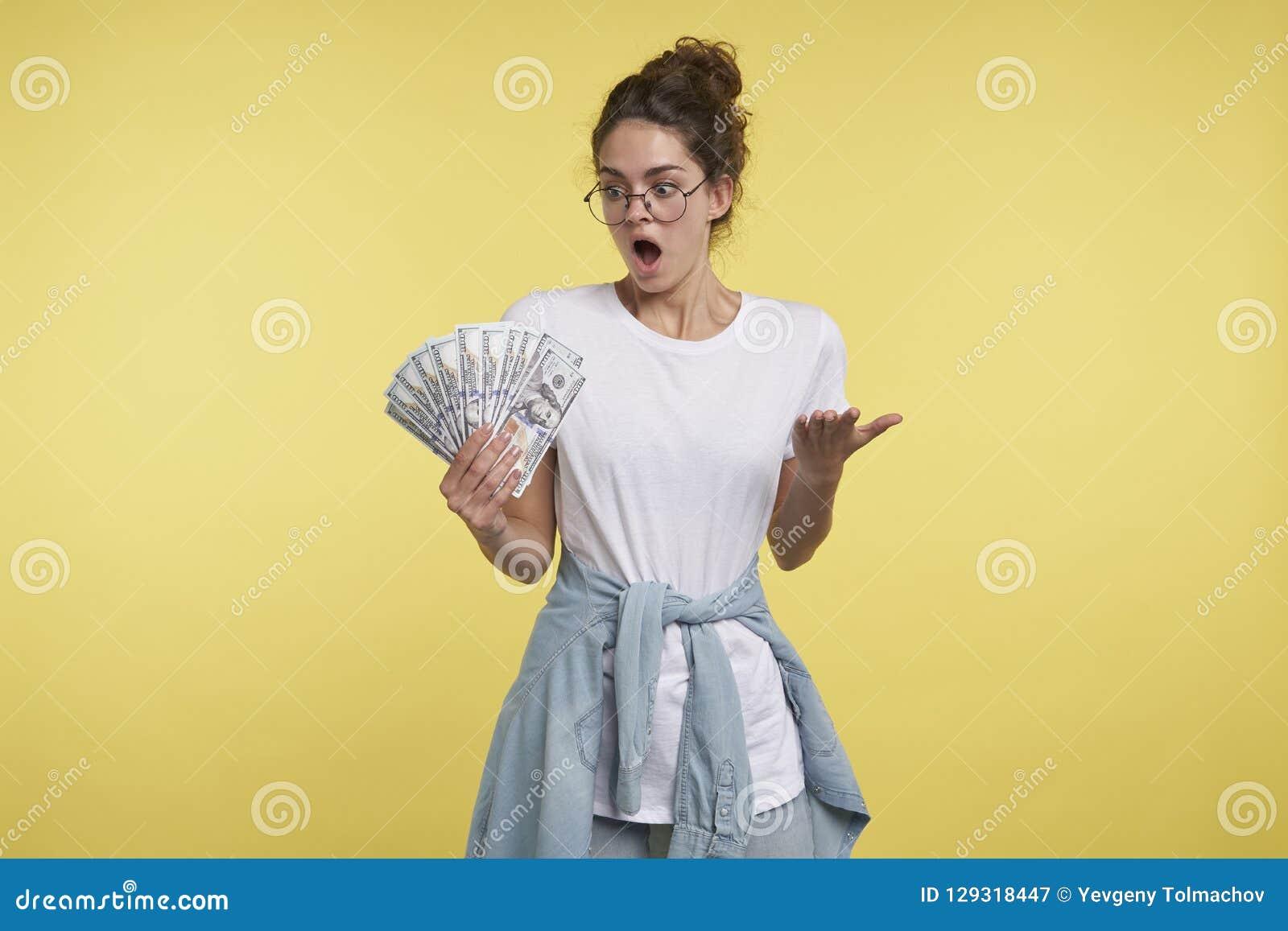 Un portrait de femme choquée de brune, elle peut le ` t la croire a tellement l argent dans la main