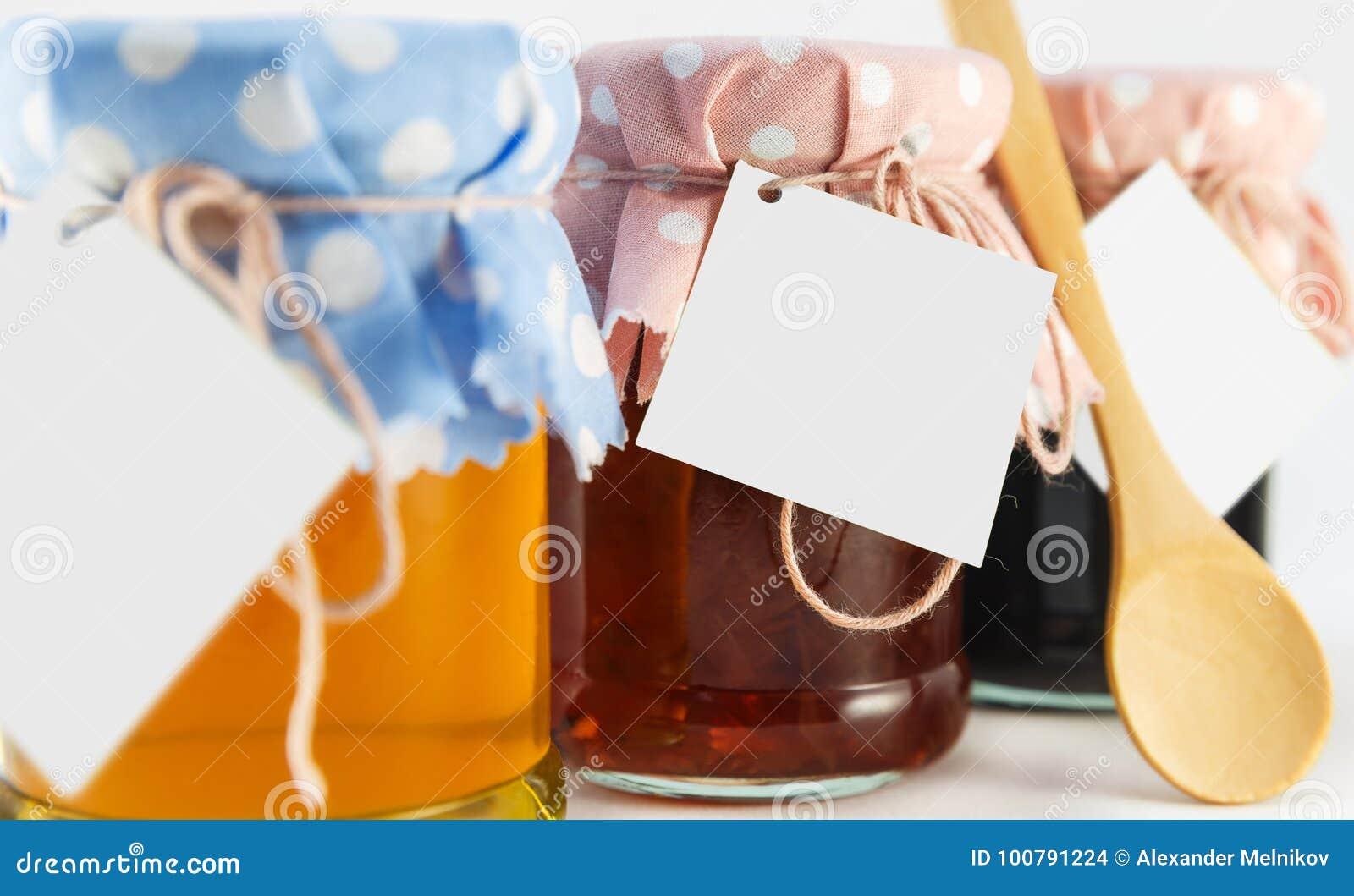 Un pot avec du miel, la mûre et la fleur bloquent sur un fond blanc