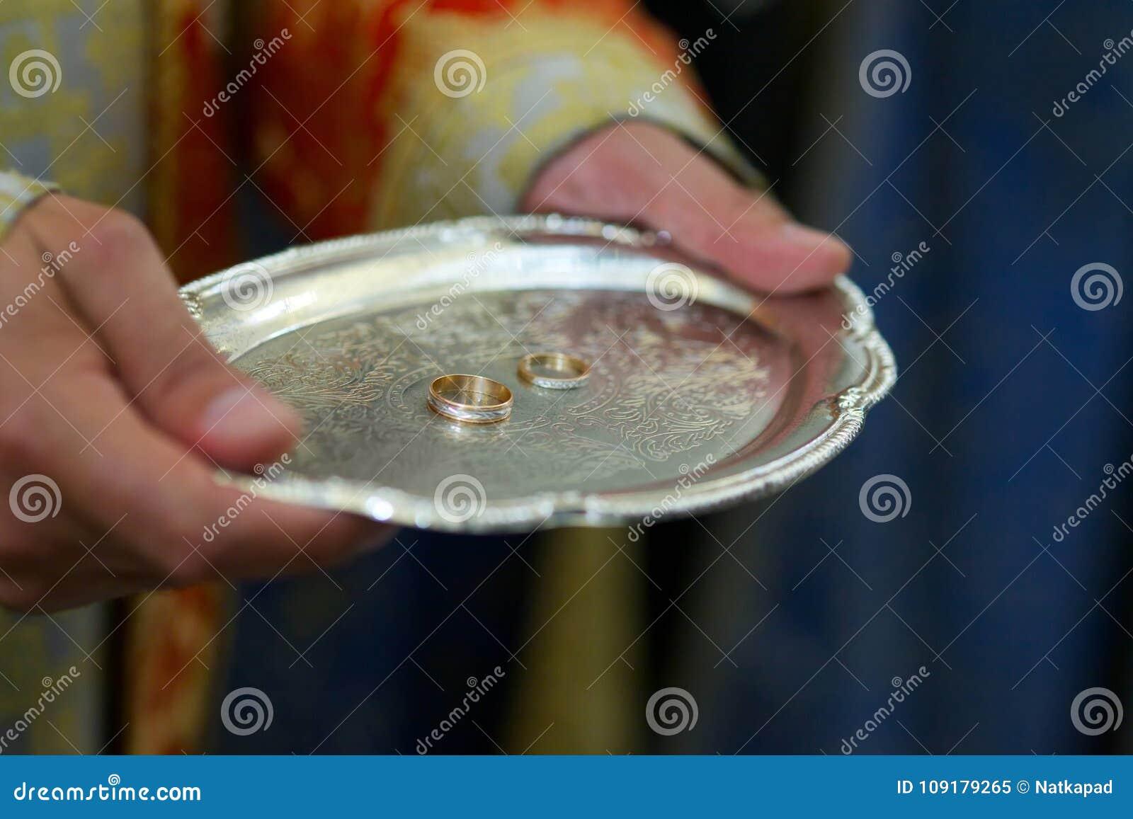 Un prêtre chrétien tient dans des ses mains un anneau de mariage