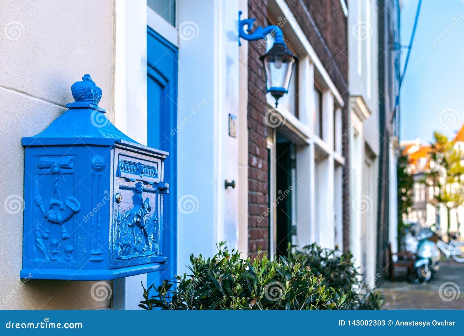 Un primer de un buzón holandés azul profundo hermoso adornado con un bajorrelieve con una opinión de la calle en el fondo