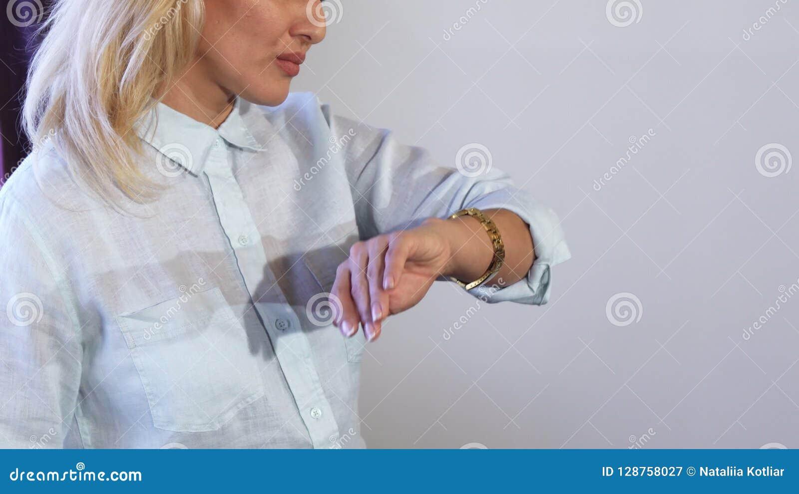 Un primer muestra a ` s de la muchacha el cuerpo superior y la mano cuando ella mira en ese entonces en su reloj
