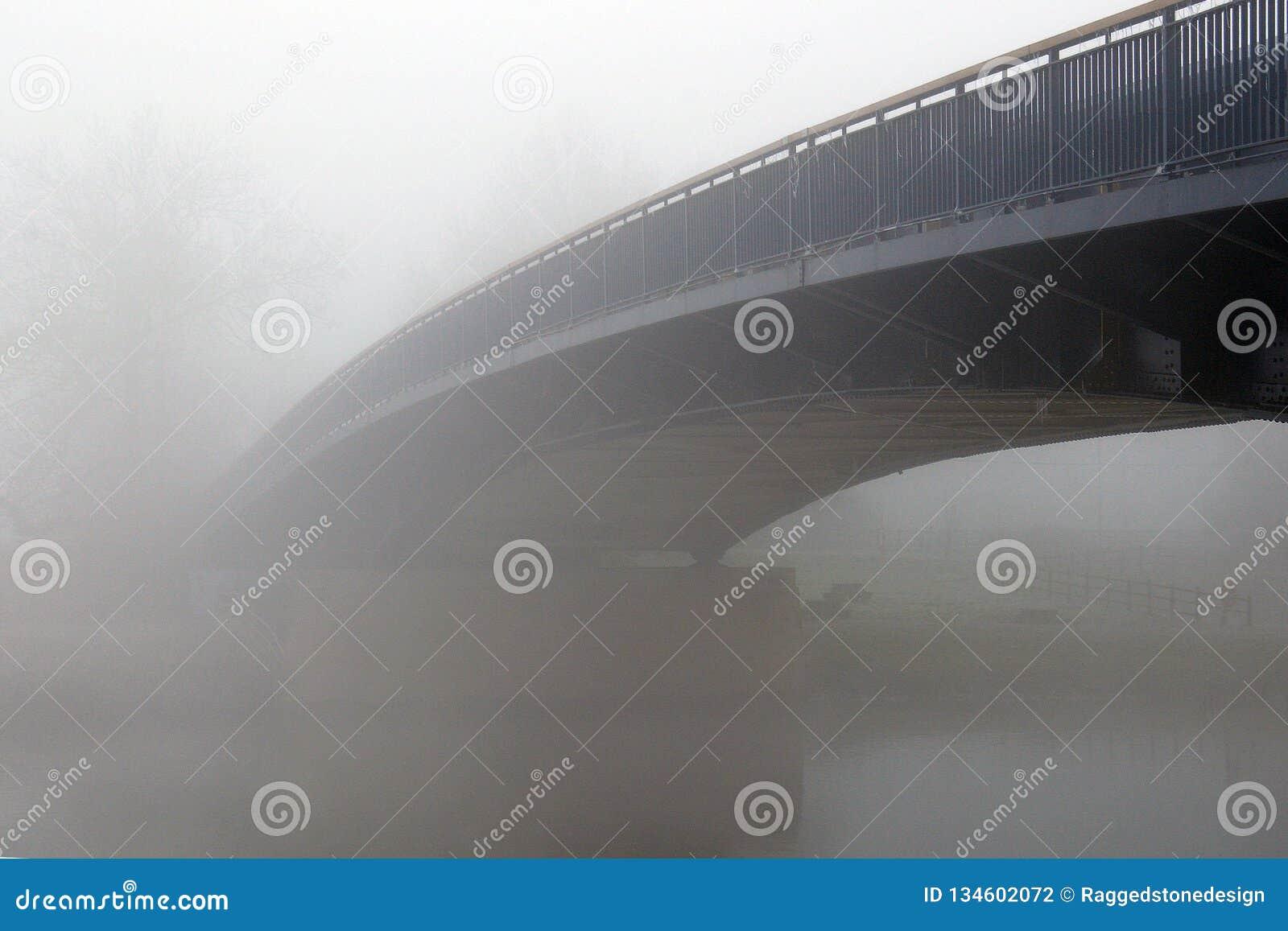 Un puente sobre un río, desapareciendo en la niebla en un día de inviernos frío Upton Upon Severn, Worcestershire, Reino Unido