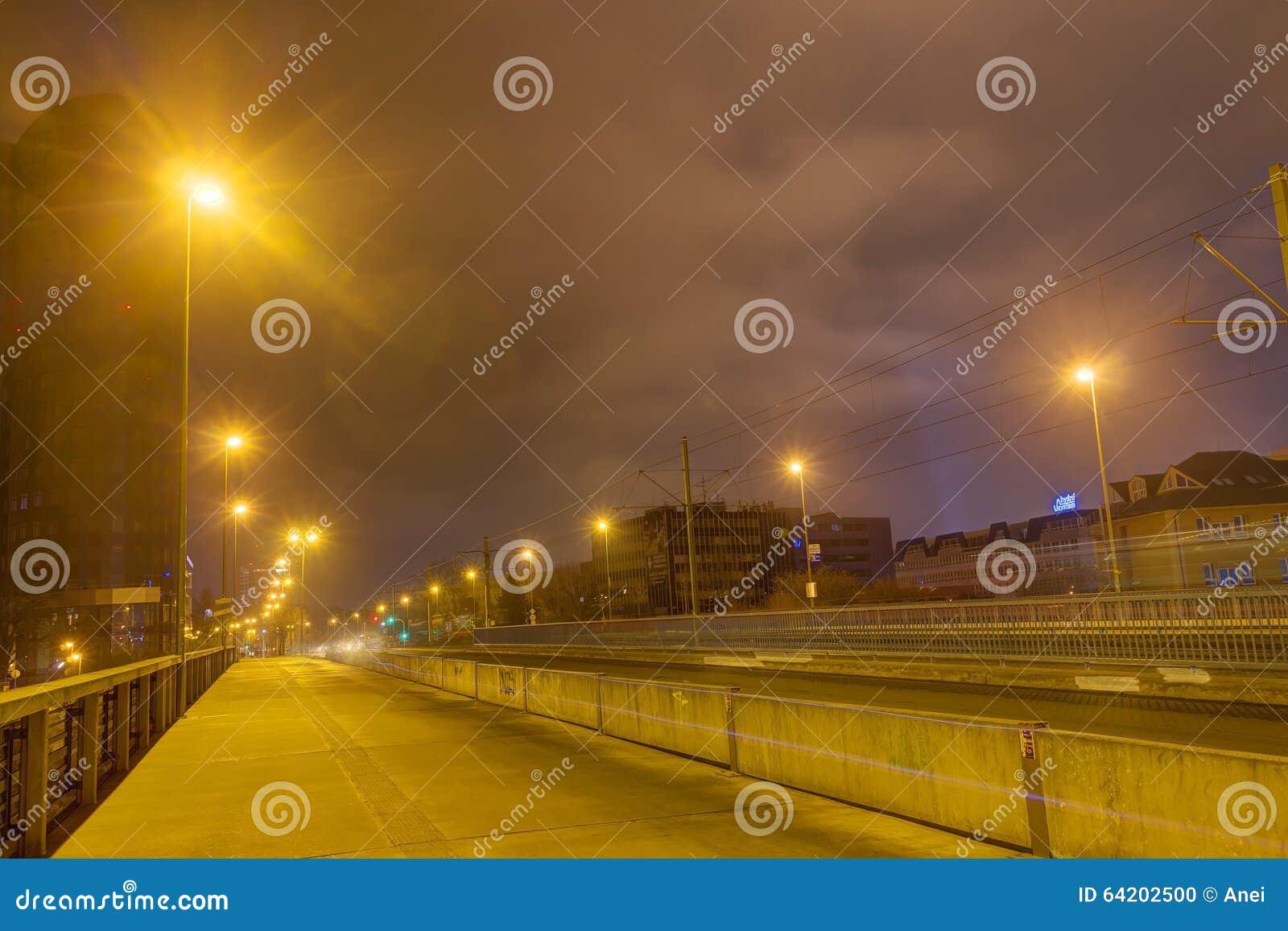 Un puente y un camino en la noche con las luces brillantes en ambos lados