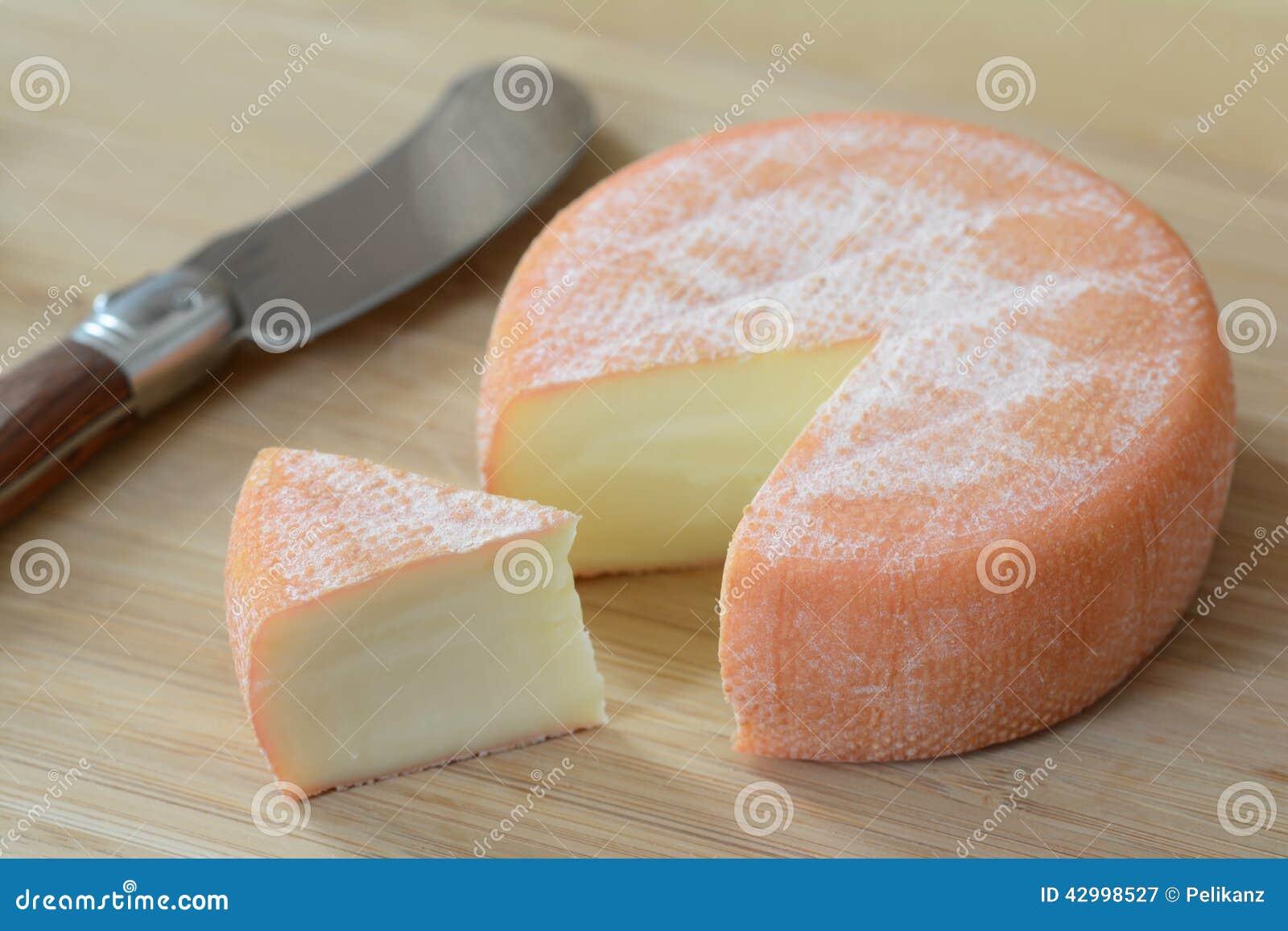 Un queso lleno del brie de la rueda con una rebanada del for Cuchillo de queso