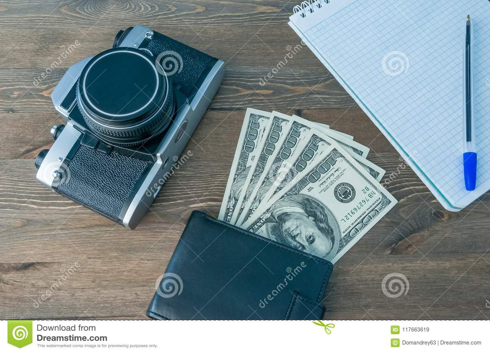Un rétro appareil-photo, une bourse avec l argent et un carnet avec un stylo sur une table en bois