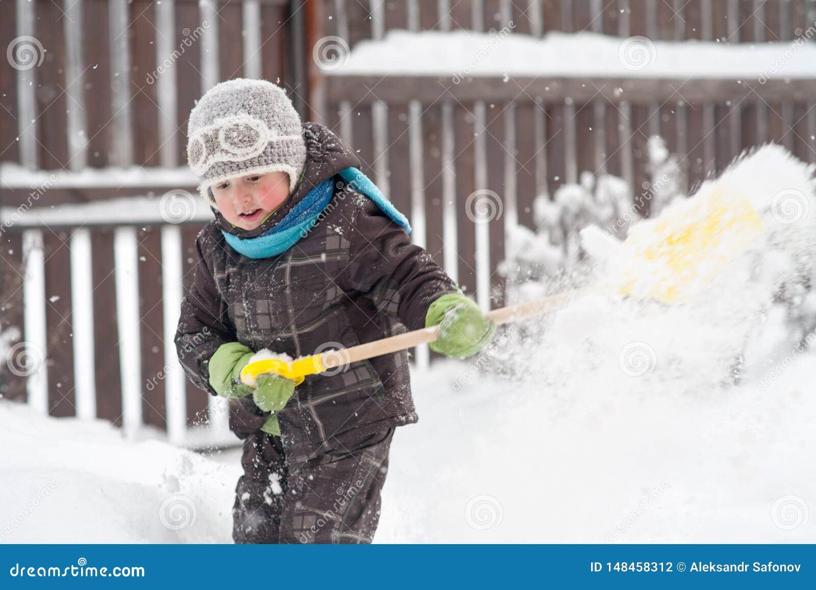 Un ragazzino libera i percorsi di una pala nell iarda da neve