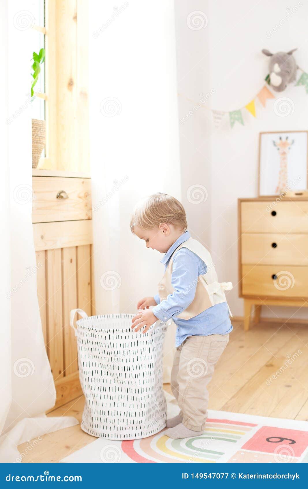Un ragazzino mette i giocattoli in un canestro scandinavo per una stanza dei bambini La stanza del bambino ecologica della decora