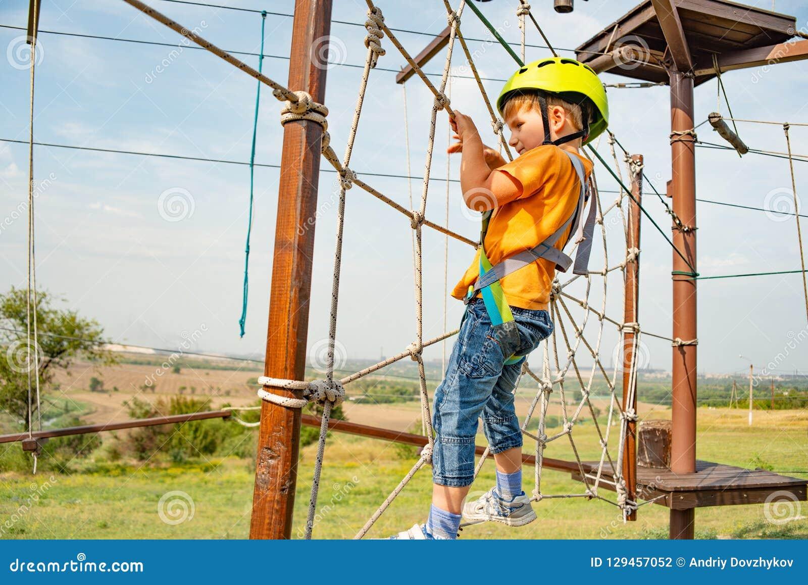 Un ragazzo in un casco giallo supera un ostacolo sulla cabina di funivia in un parco estremo