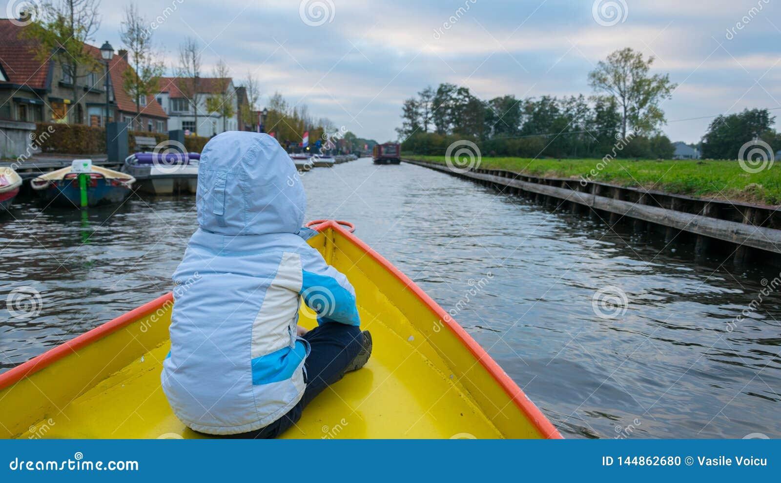 Un ragazzo con una giacca blu con il suo indietro sulla parte anteriore della barca sui canali dell acqua in Giethoorn, Paesi Bas