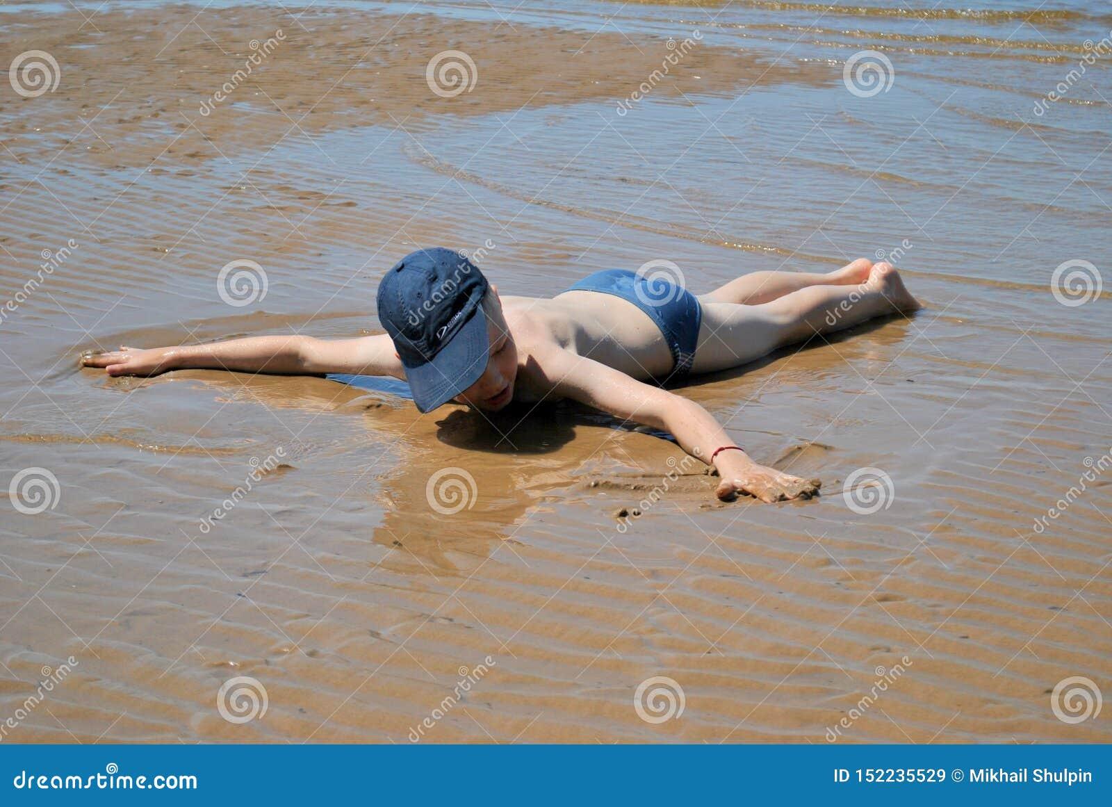 Un ragazzo in costume da bagno ed in un cappuccio si trova fronte giù su una spiaggia sabbiosa dopo una bassa marea, con le sue a