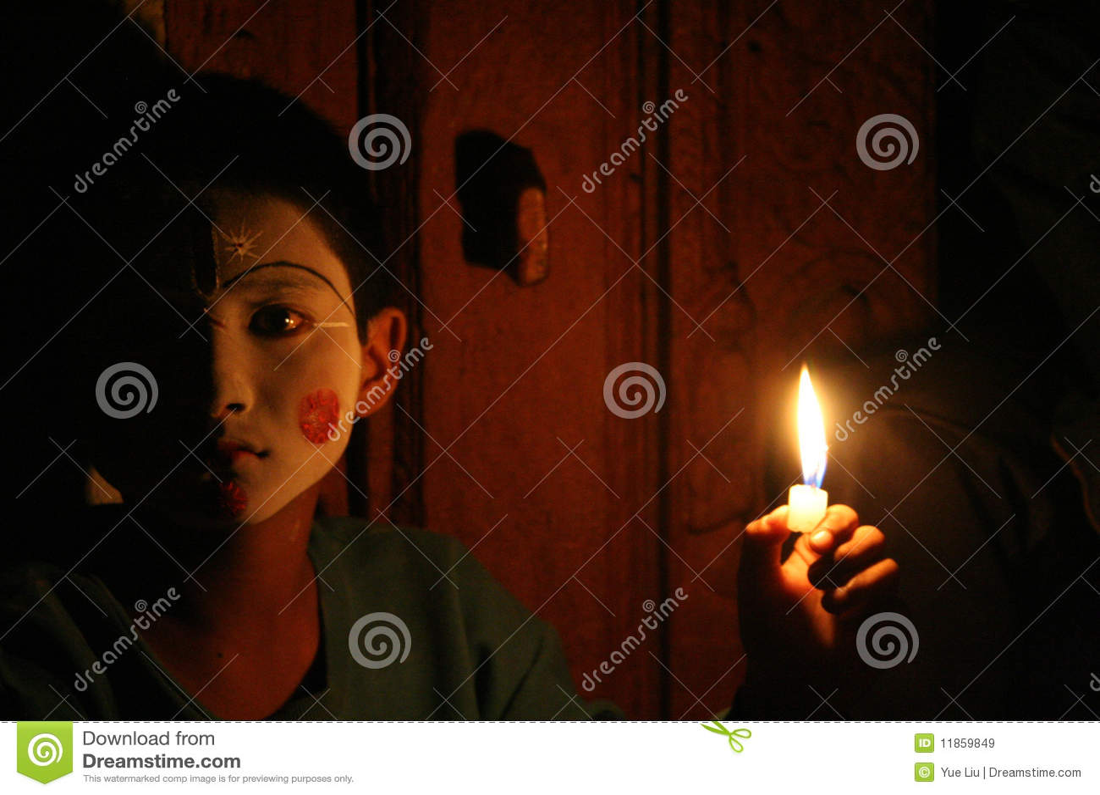 Un ragazzo del Nepali nel trucco che tiene una candela