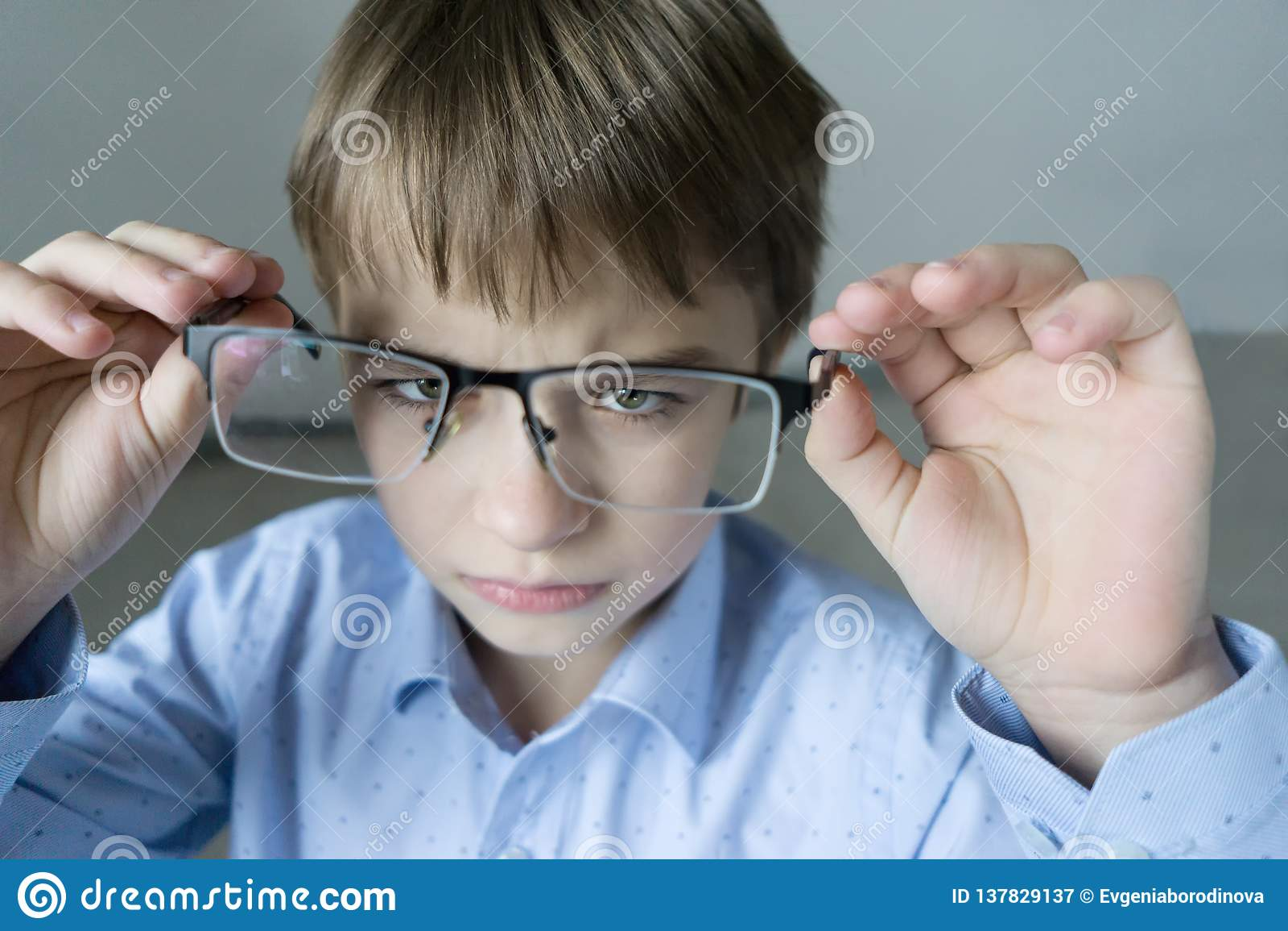 Un ragazzo di 9 anni in una camicia blu con i vetri controlla la sua vista Insoddisfatto con il fatto che ha prescritto i vetri -