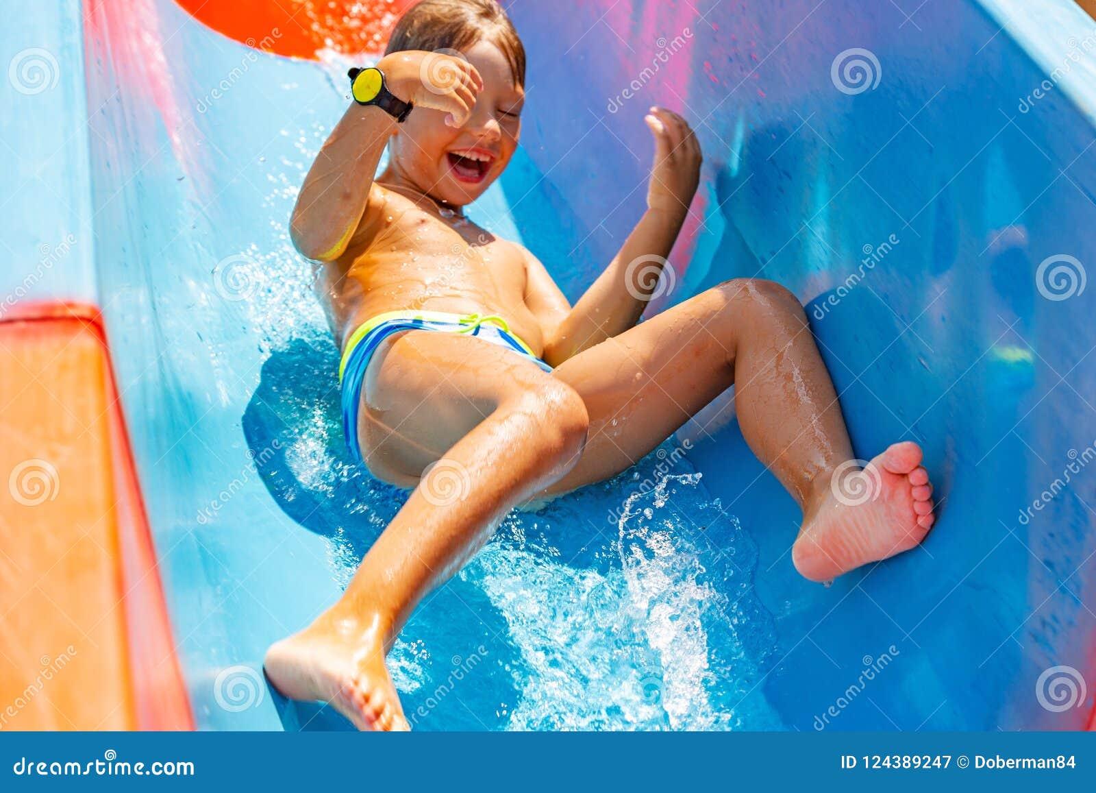 Un ragazzo felice sull acquascivolo in una piscina che si diverte durante le vacanze estive in bella acqua parcheggia un ragazzo
