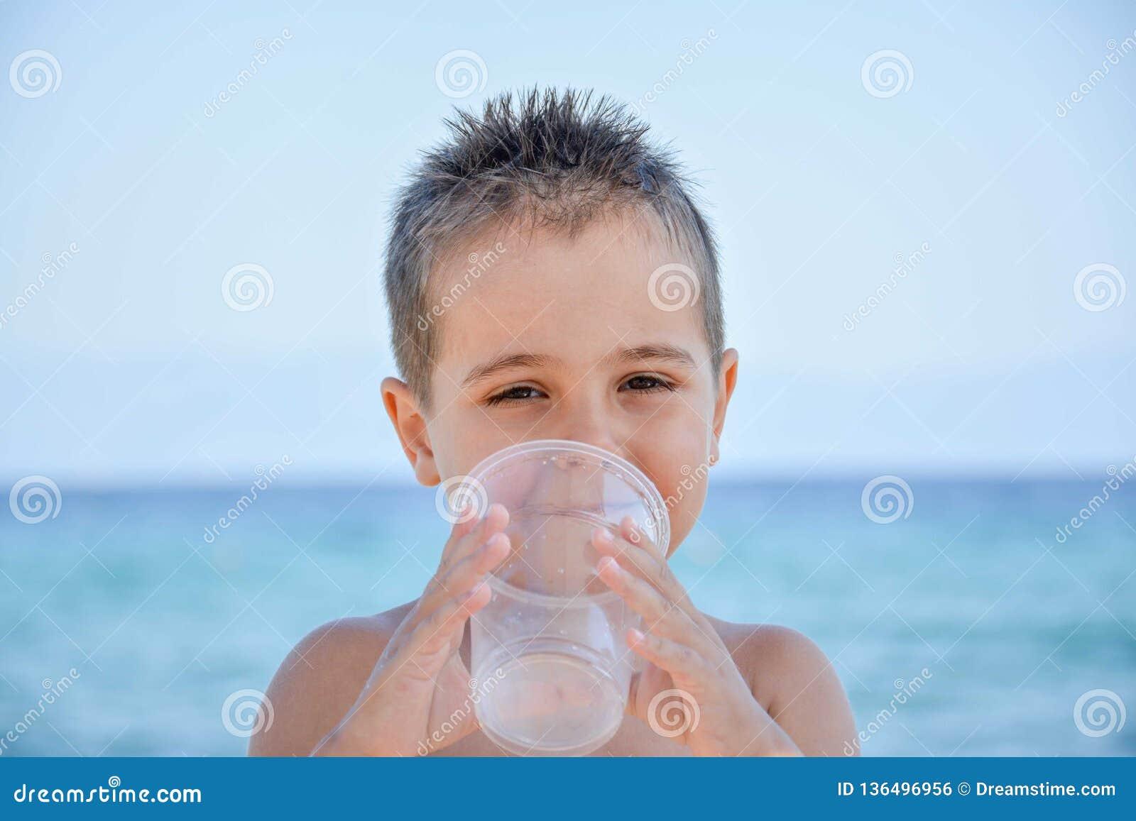 Un ragazzo sveglio che posa sulla spiaggia