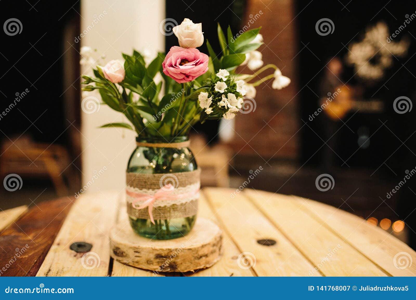 Un ramo de flores está en el banco, la rosa está en el foco, todo lo demás es un poco borroso