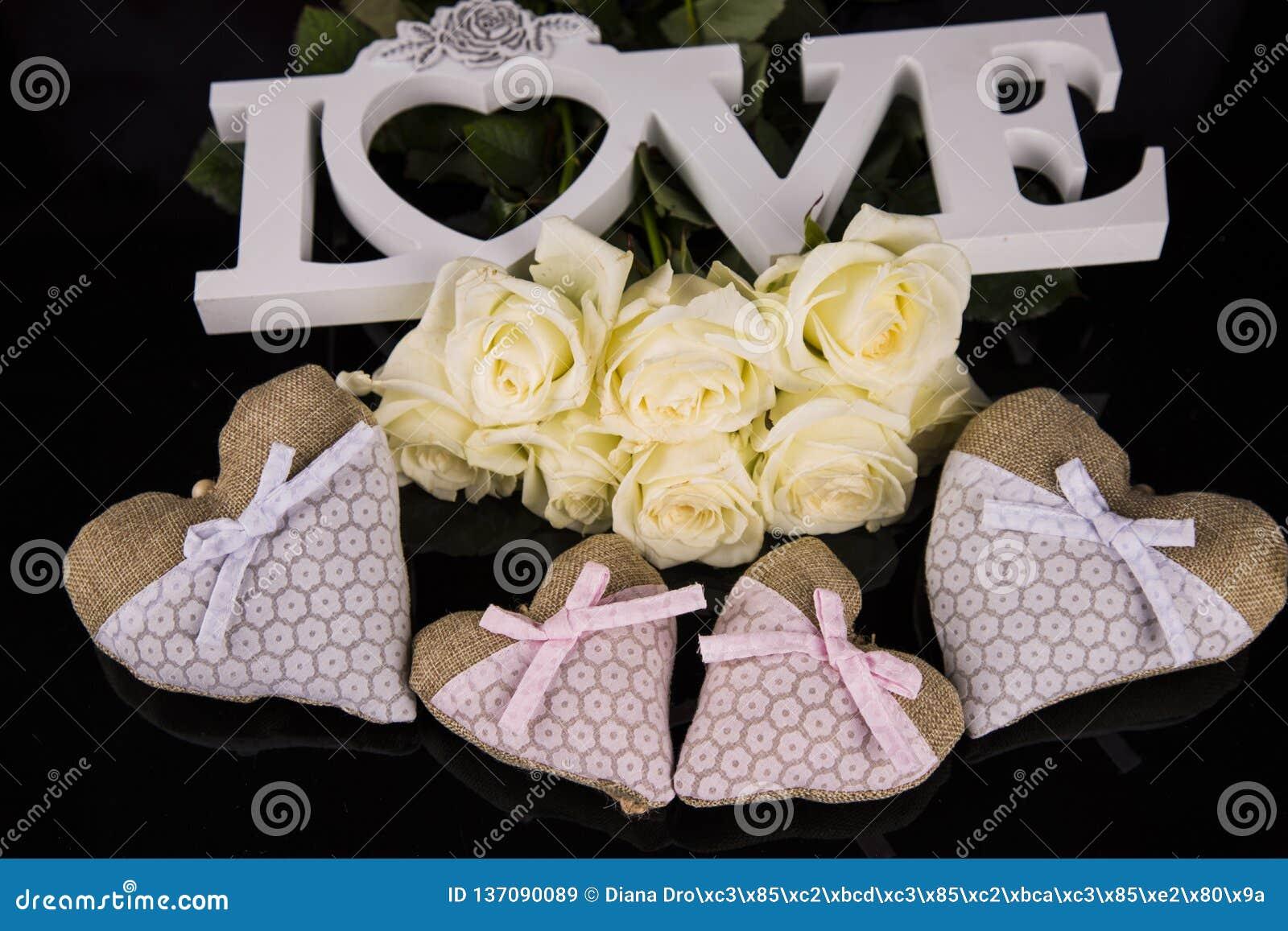 Un ramo de rosas blancas, corazones hizo del material, ángeles valentines