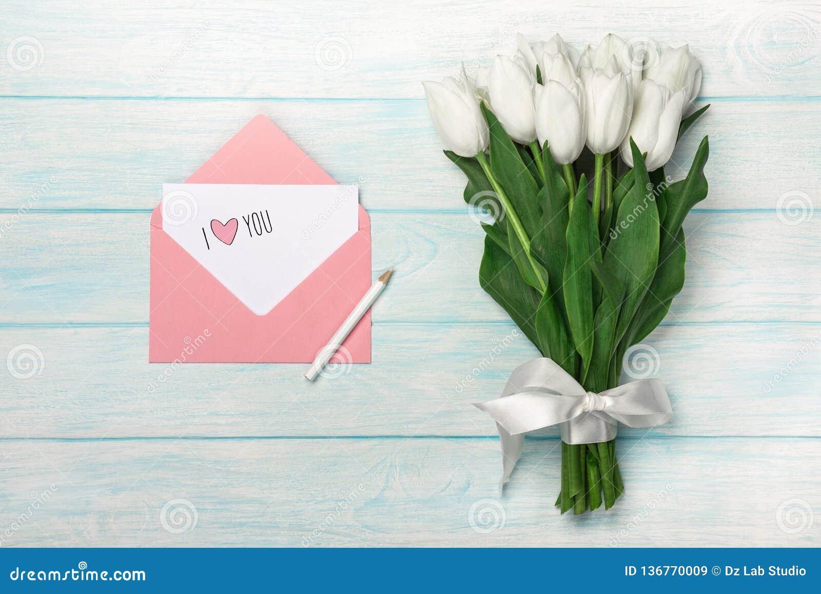 Un ramo de tulipanes blancos con la nota del amor y el sobre del color en los tableros de madera azules
