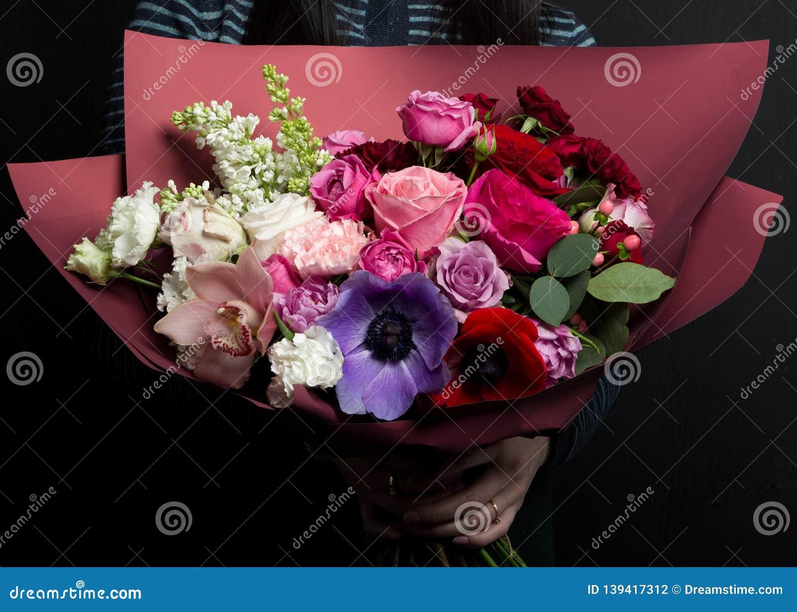 Un ramo hermoso de flores raras con las anémonas, ranúnculo, claveles, lila, en las manos de una muchacha