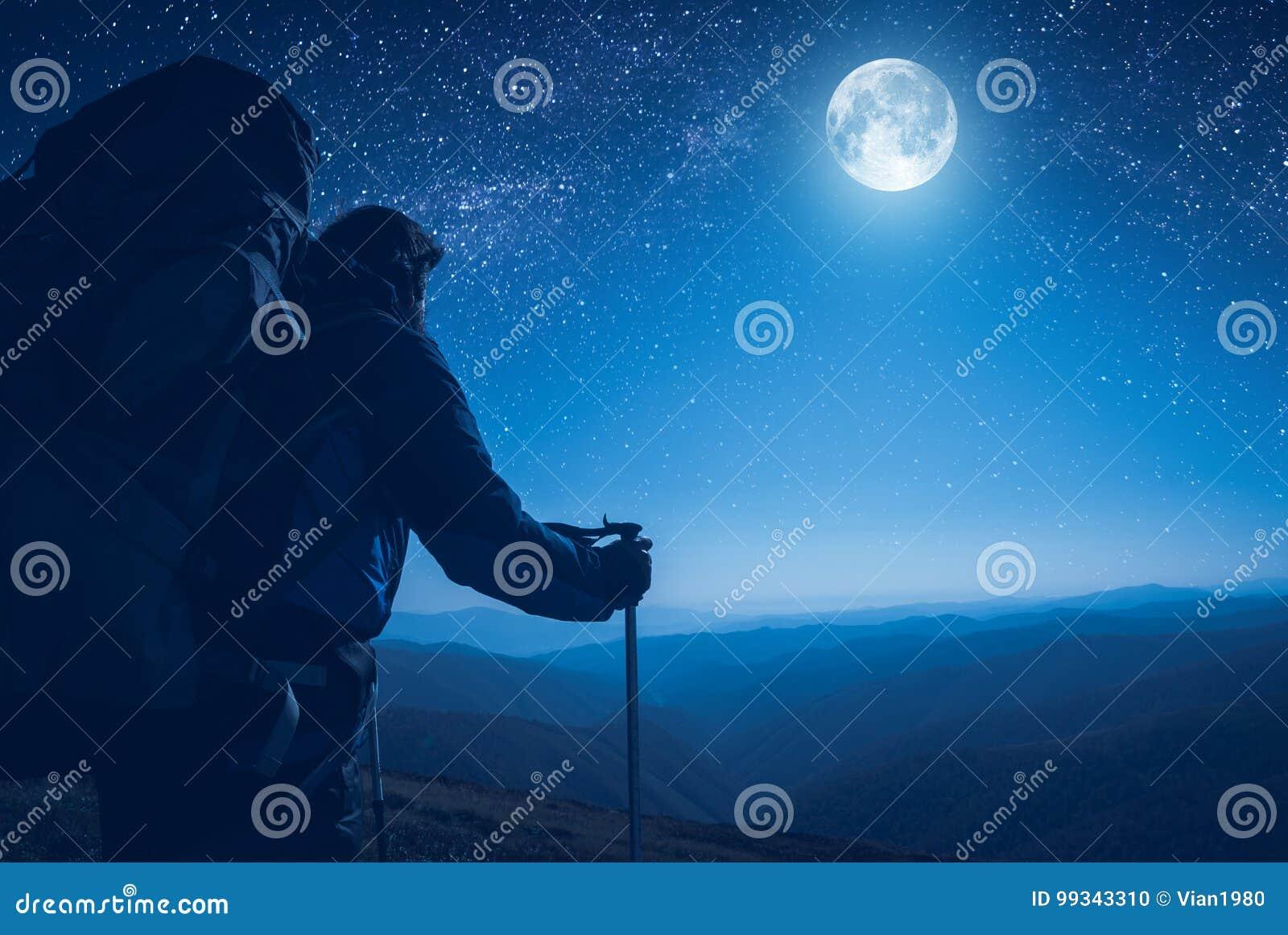 Un randonneur contemplent la pleine lune