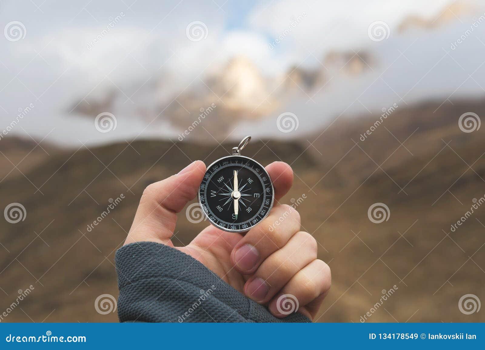 Un randonneur masculin recherche une direction avec une boussole magnétique dans les montagnes en automne Tir de point de vue ` S