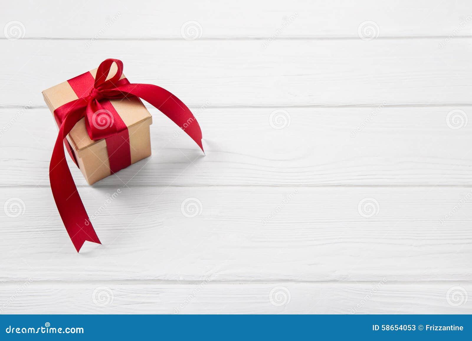 Un regalo de Navidad rojo en el fondo de madera blanco con un grande