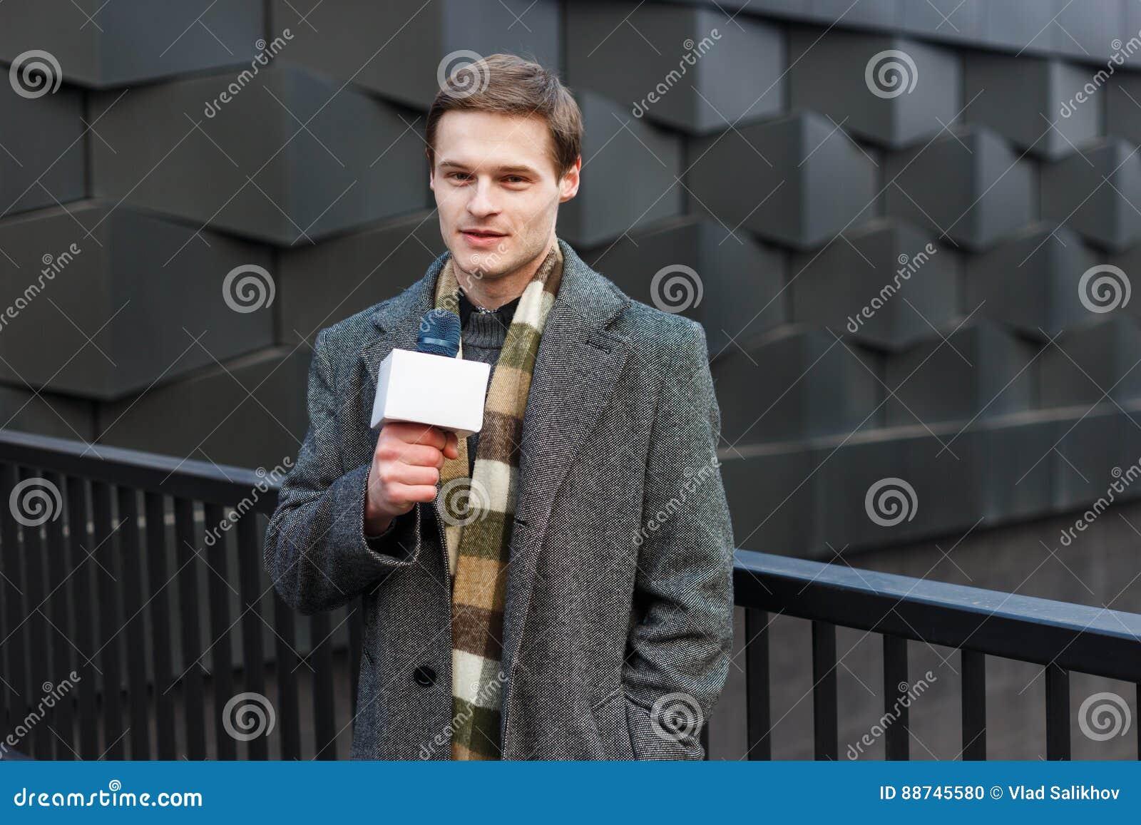 Un reporter maschio alla moda vestito dei giovani TV sta riferendo sulla via nella città