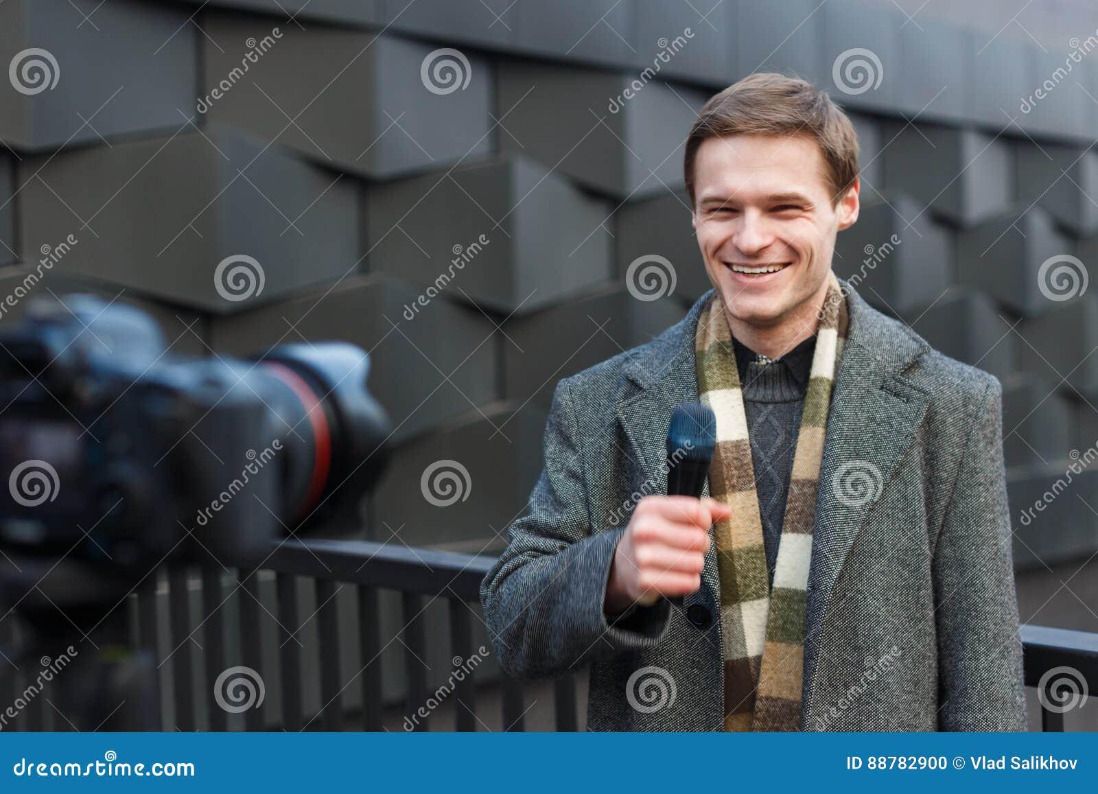 Un reporter maschio felice conduce un rapporto sulla macchina fotografica sulla via