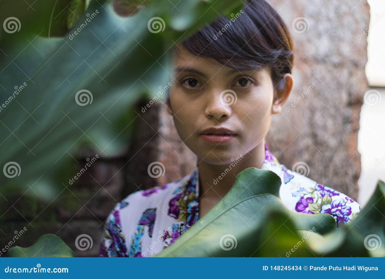 Un retrato de una mujer de pelo corto hermosa con una flor en su o?do Ella est? llevando un vestido de Bali con los adornos flora