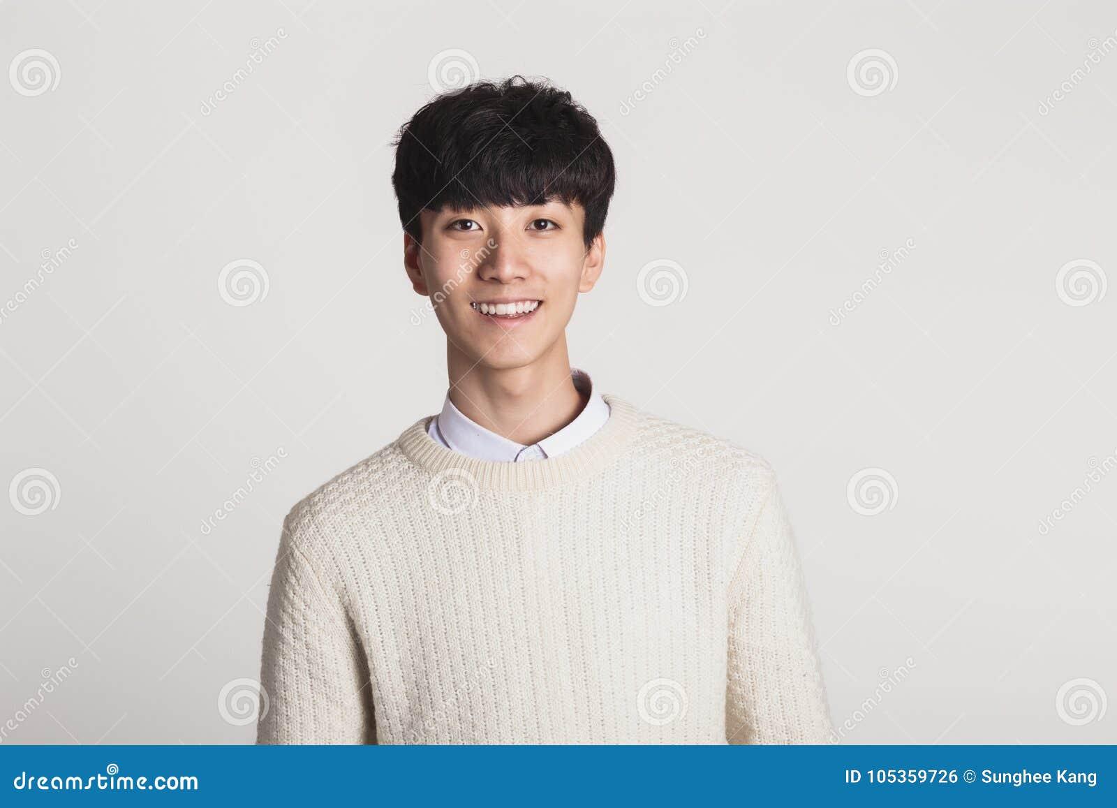 Un retrato del estudio de un hombre joven asiático que busca una cámara con sonrisas confiadas