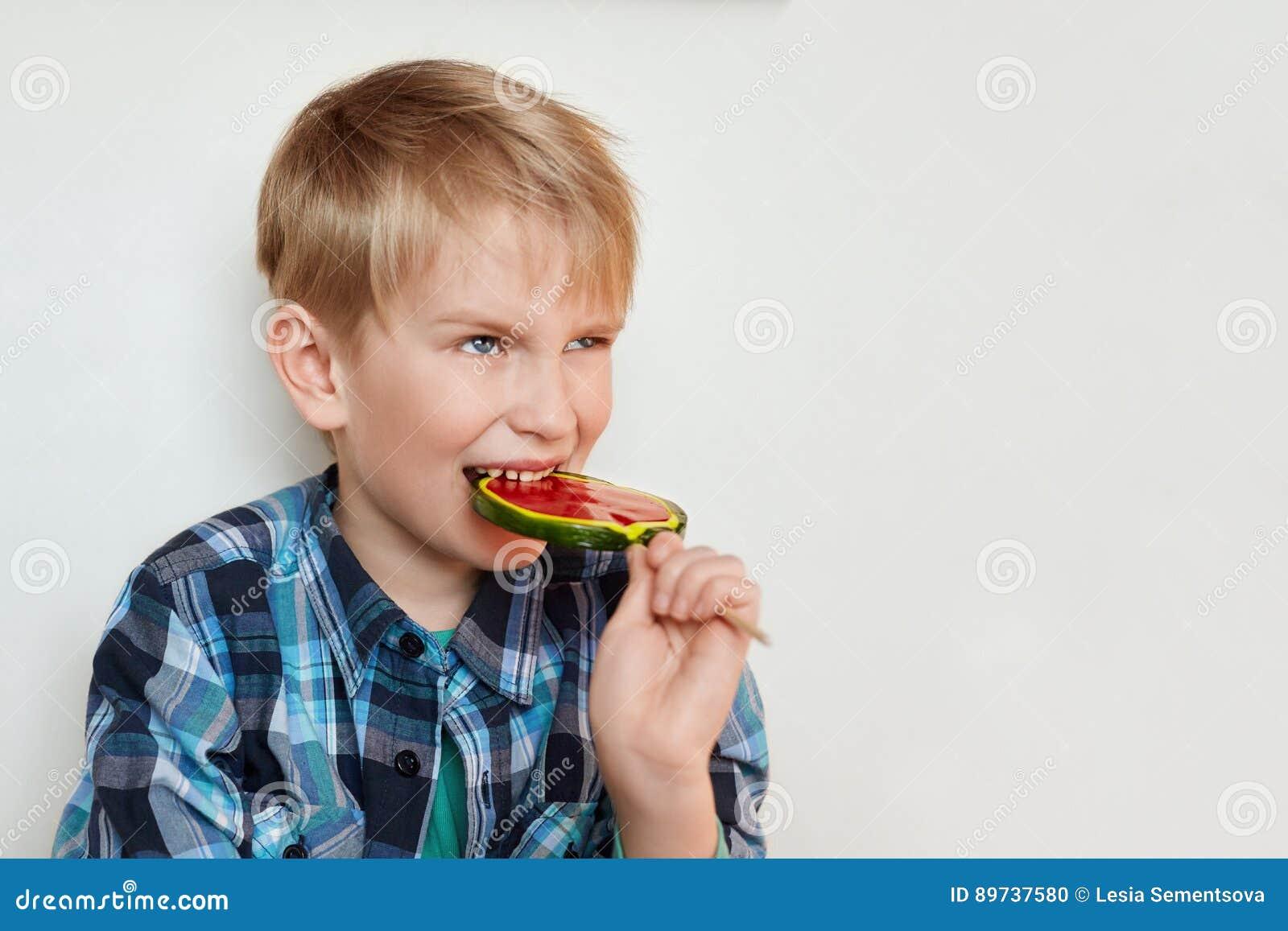 Un retrato del niño emocional con el pelo justo se vistió en la piruleta  colorida grande d4a82b19f05