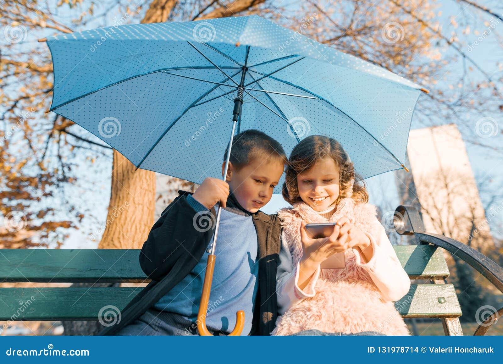 Un ritratto all aperto di due bambini sorridenti del ragazzo e della ragazza, sedentesi sotto un ombrello sul banco nel parco, es