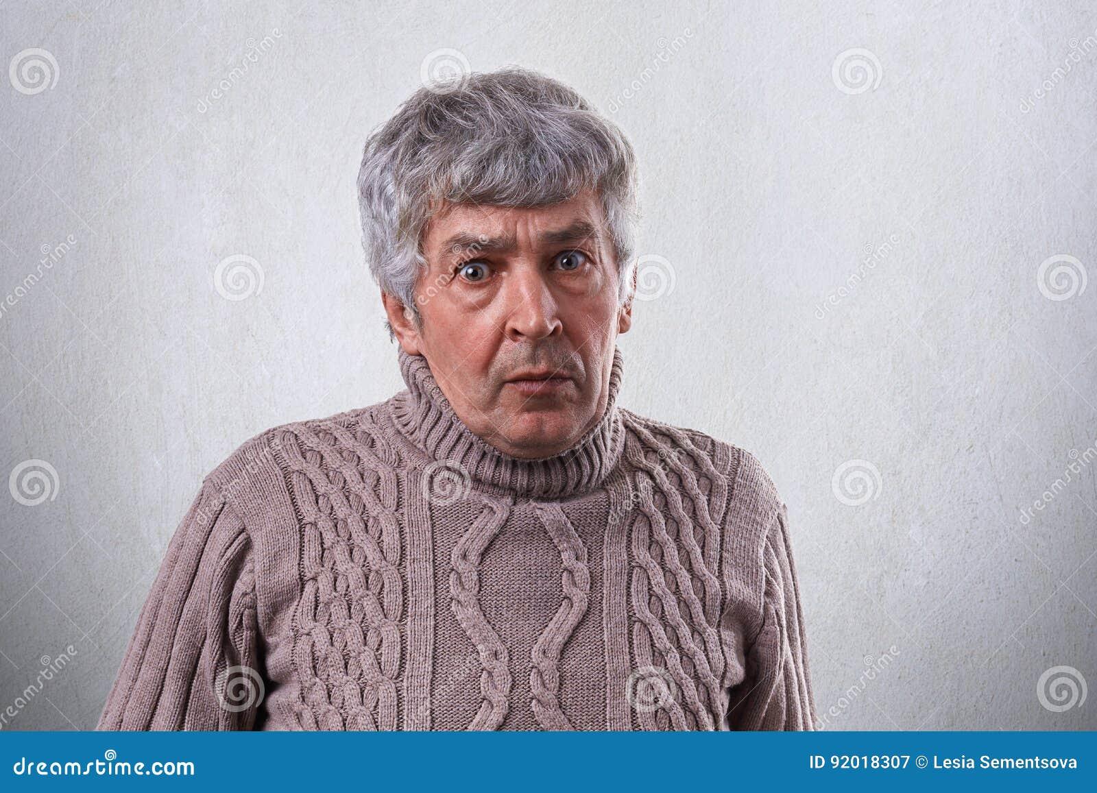 Un ritratto dell uomo maturo stupito con il maglione d uso dei capelli grigi  che guarda con gli occhi spalancati nella macchina fotografica mentre  posando ... d3cc4f34d3ca